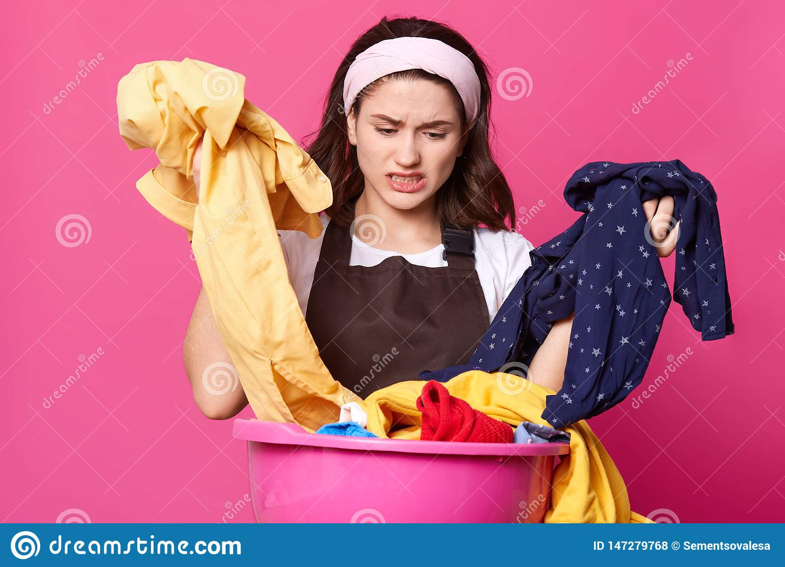 Bandeau de jeune dame et T-shirt blancs de port émotifs déçus, tablier brun, ayant l expression du visage désagréable, assortissa