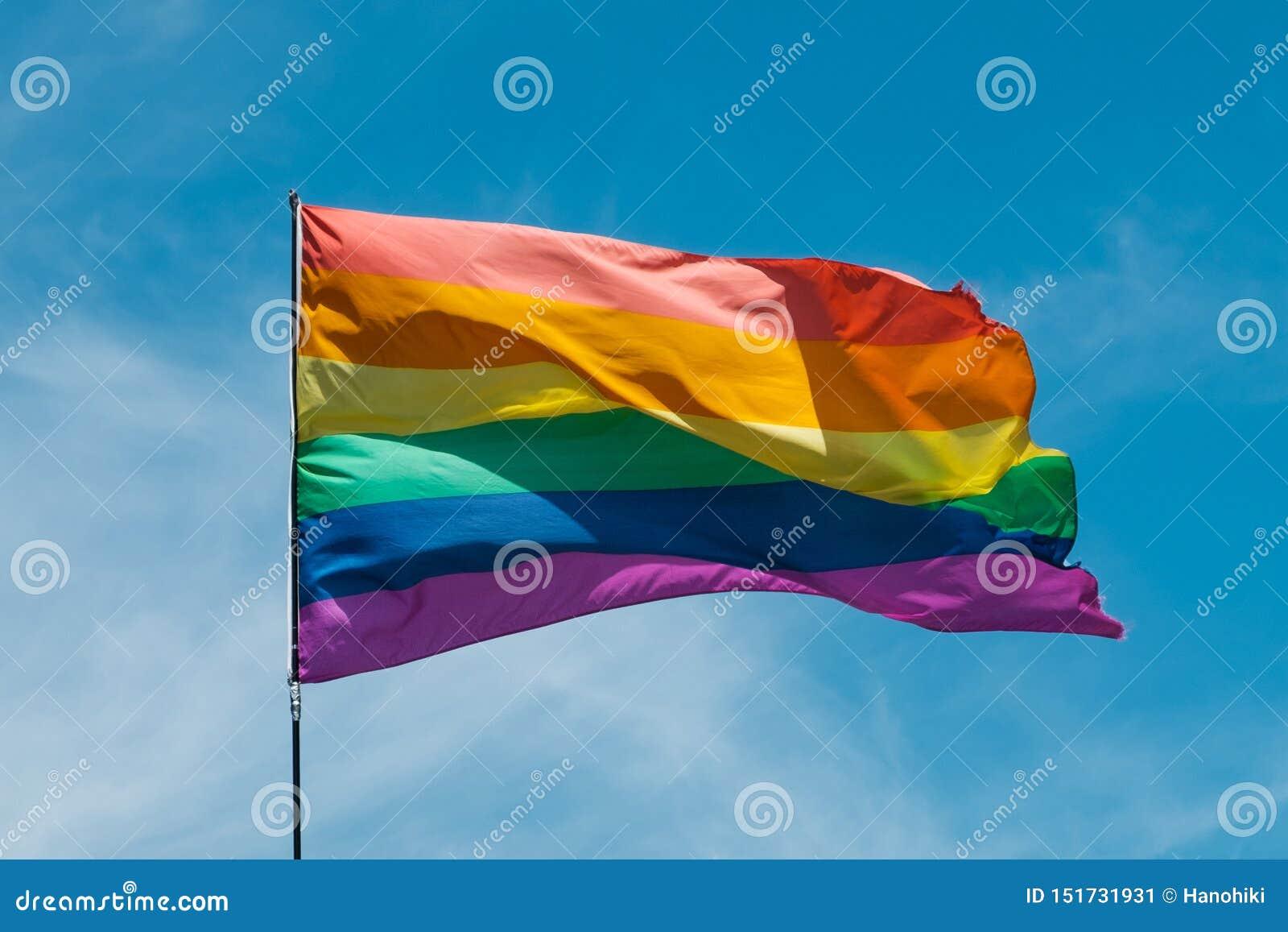 Bandeira alegre do arco-íris que acena com fundo do céu azul - símbolo de Gay Pride