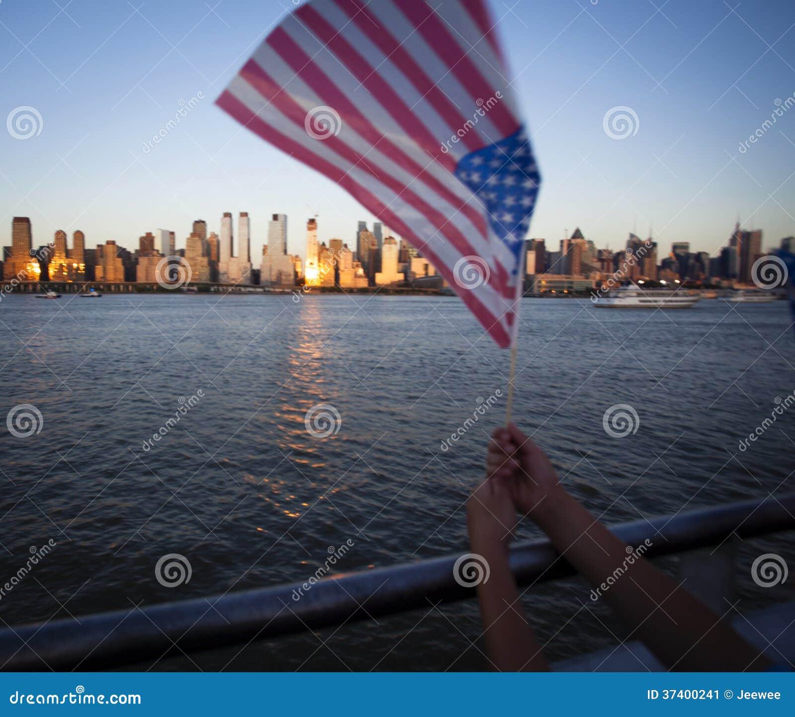 Bandeira americana durante o Dia da Independência em Hudson River com uma vista em Manhattan - New York City - Estados Unidos