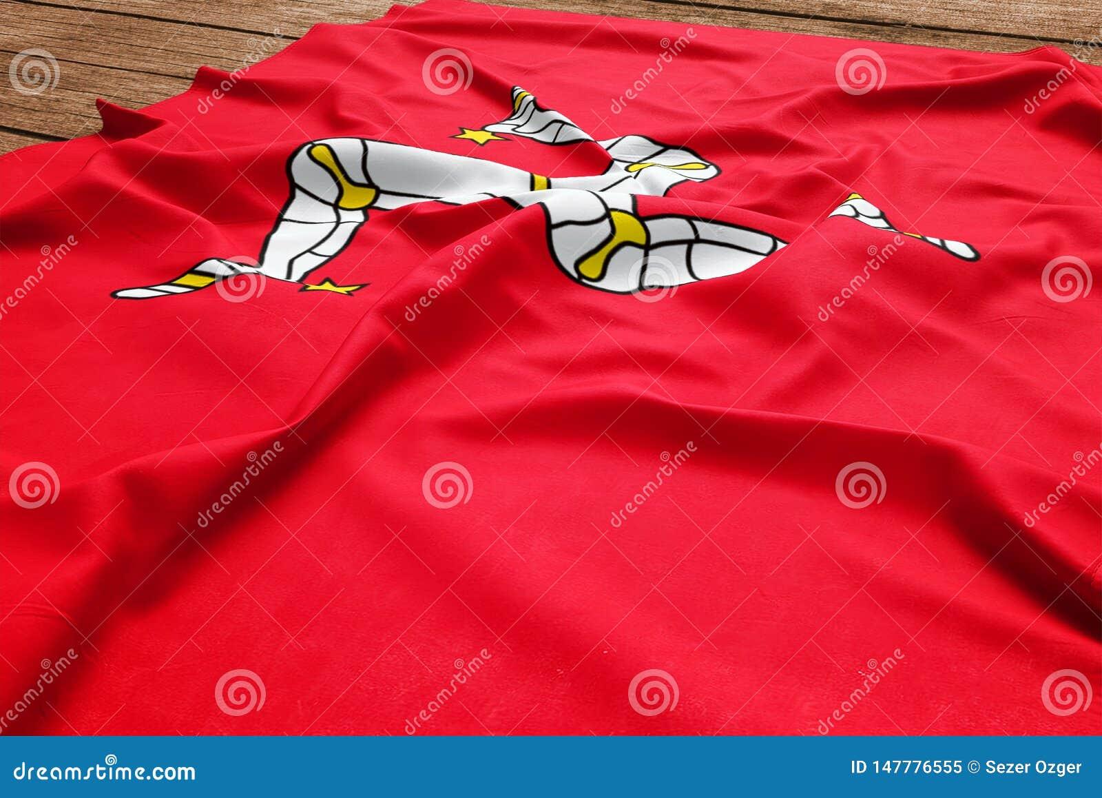 Bandeira da ilha do homem em um fundo de madeira da mesa Opini?o superior da bandeira de seda