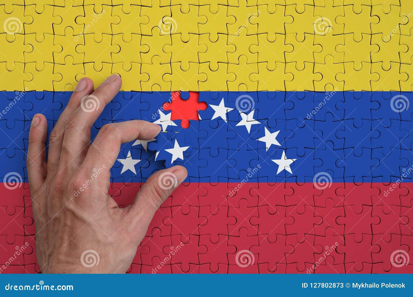 A bandeira da Venezuela é descrita em um enigma, que a mão do ` s do homem termine para dobrar