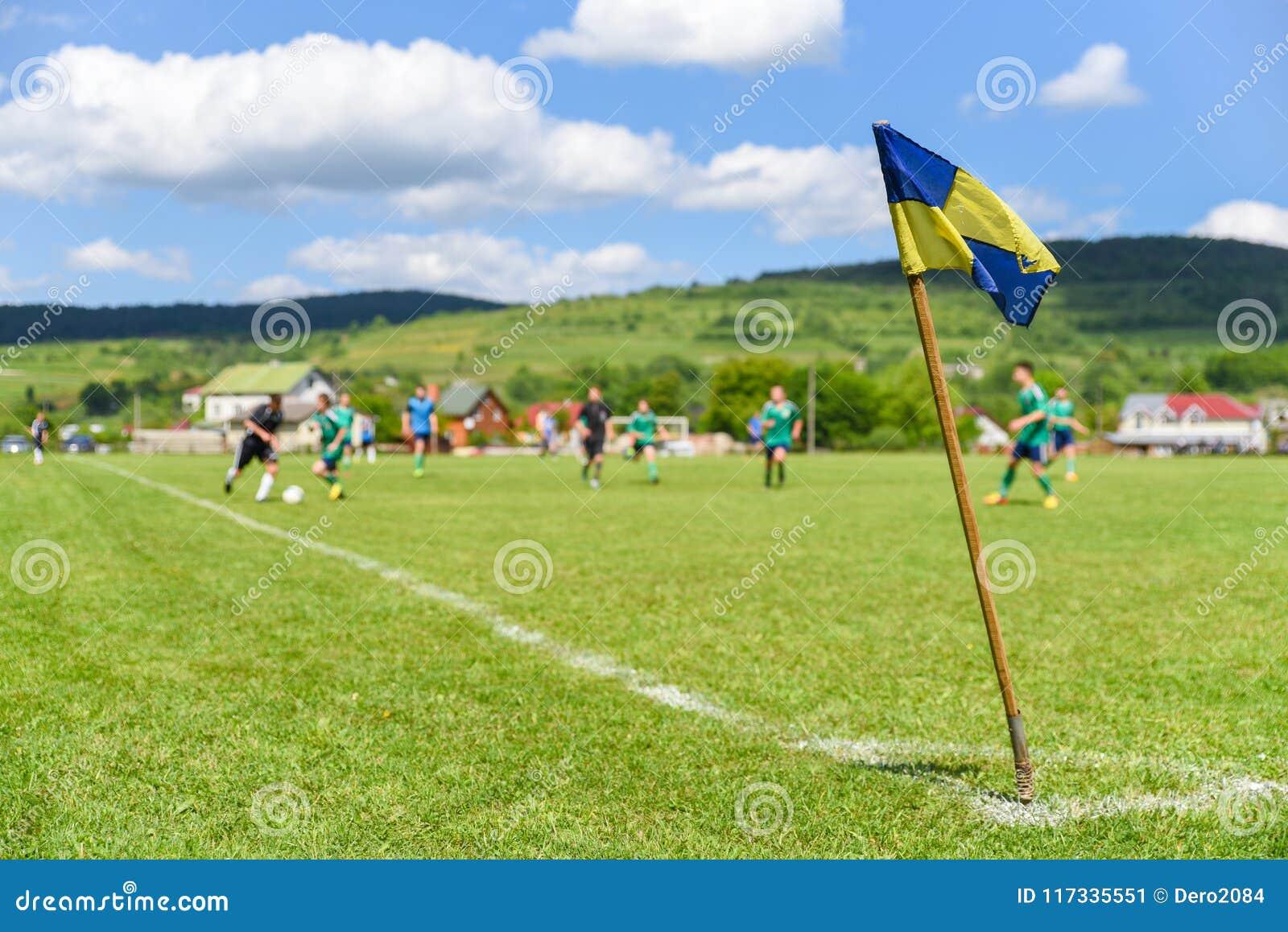 A bandeira de canto retro no primeiro plano do campo de futebol amador, no fundo obscuro é jogadores de futebol que lutam pela bo