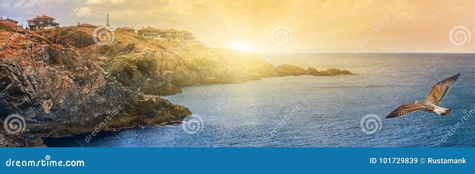Bandeira litoral da paisagem, panorama - o litoral rochoso com gaivotas e a vila de Sozopolis