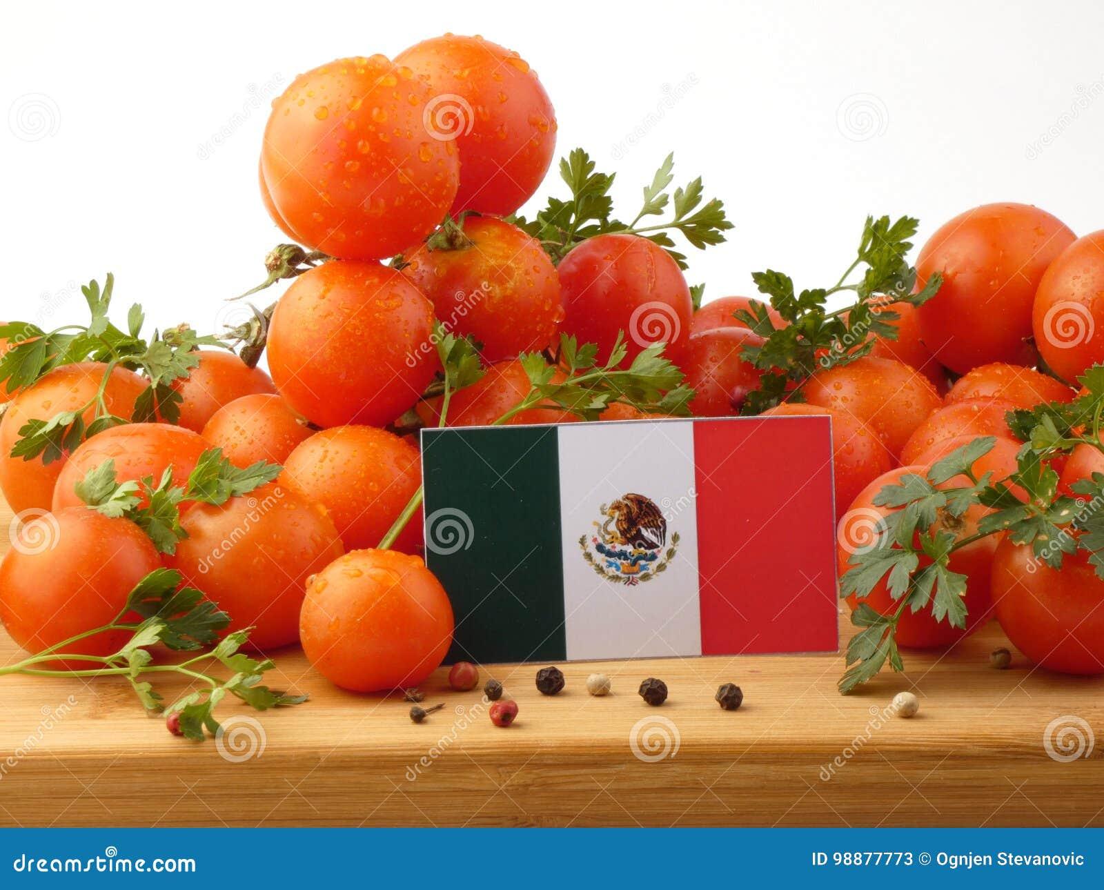 Bandeira mexicana em um painel de madeira com os tomates isolados em um branco