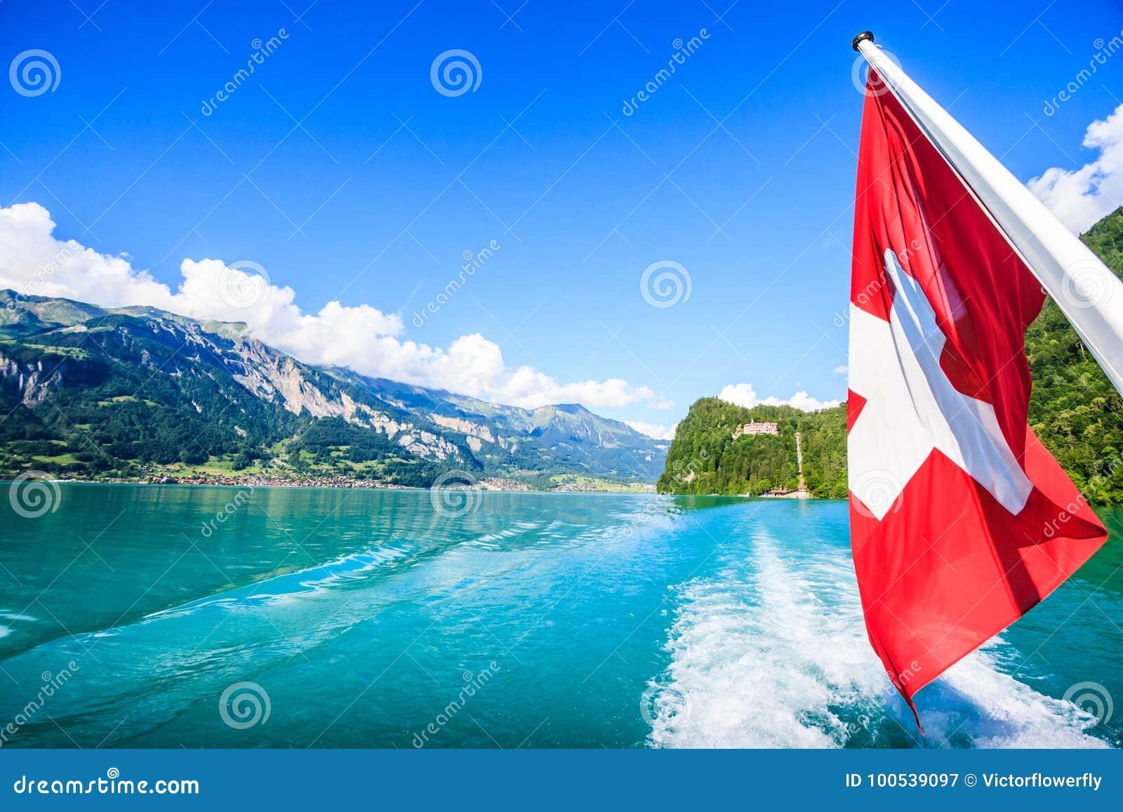 Bandeira nacional de Suíça na retaguarda do ` s do barco do cruzeiro com ideia bonita do verão do fundo natural suíço dos cumes,