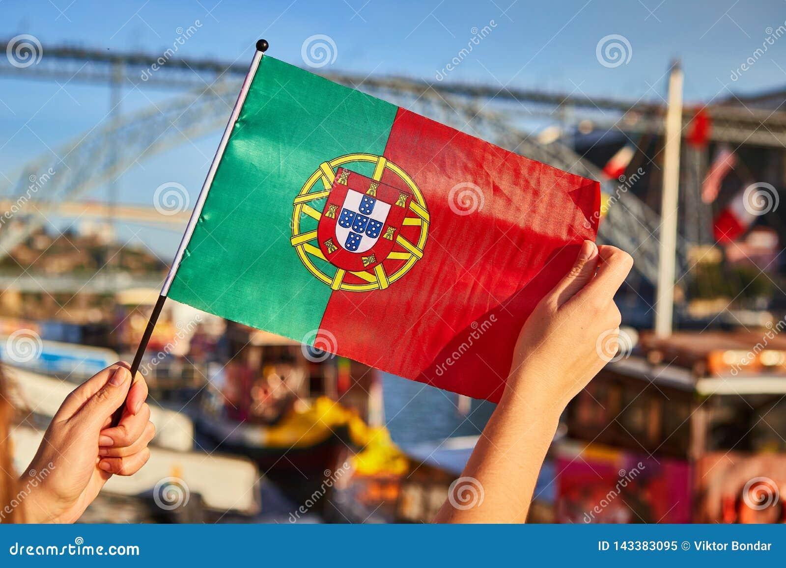 Bandeira portuguesa como um símbolo de Portugal no fundo da ponte Ponte de Dom Luis I na terraplenagem perto do rio Doure dentro
