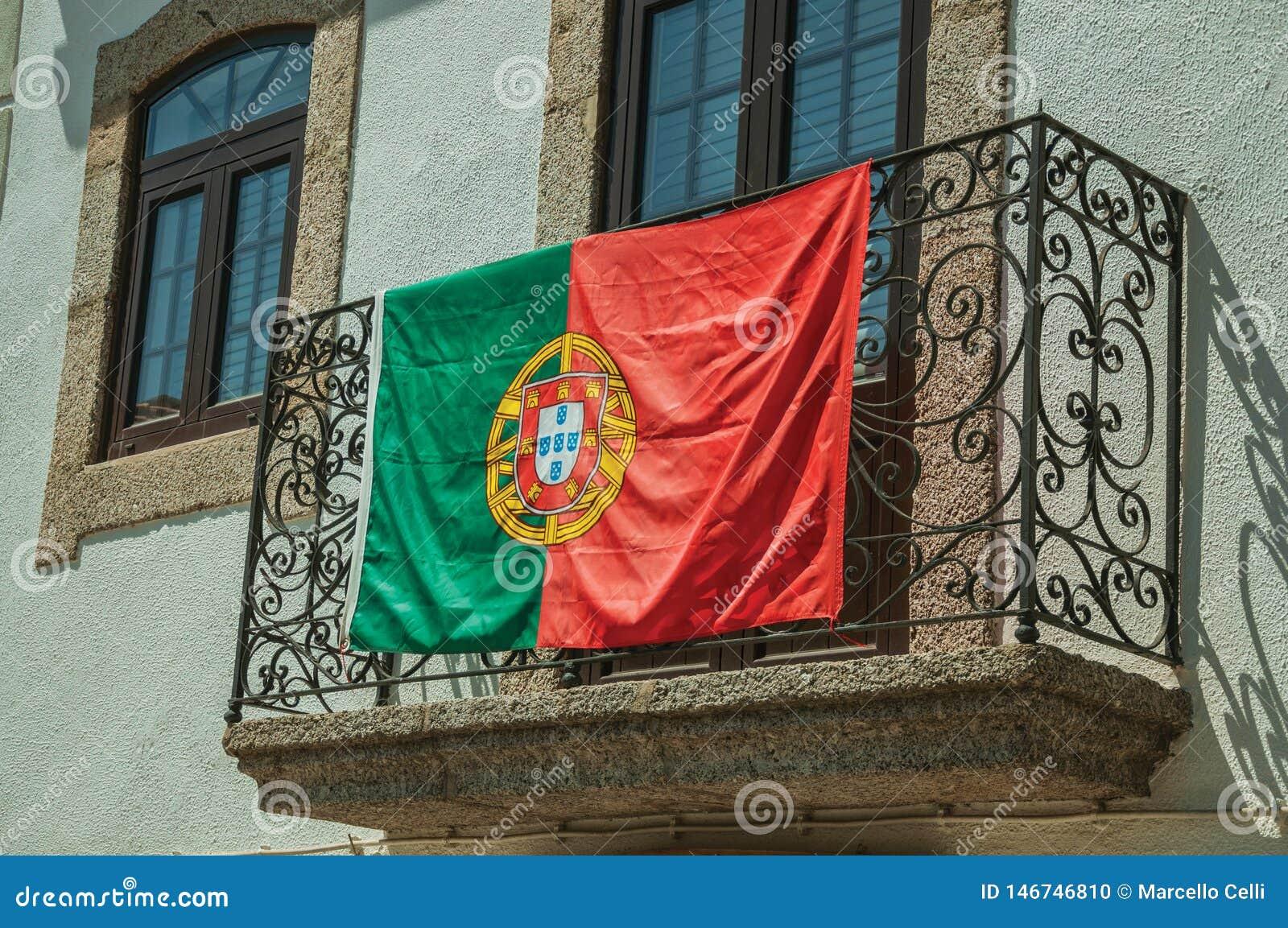 Bandeira portuguesa em trilhos do ferro em um balcão de uma construção velha