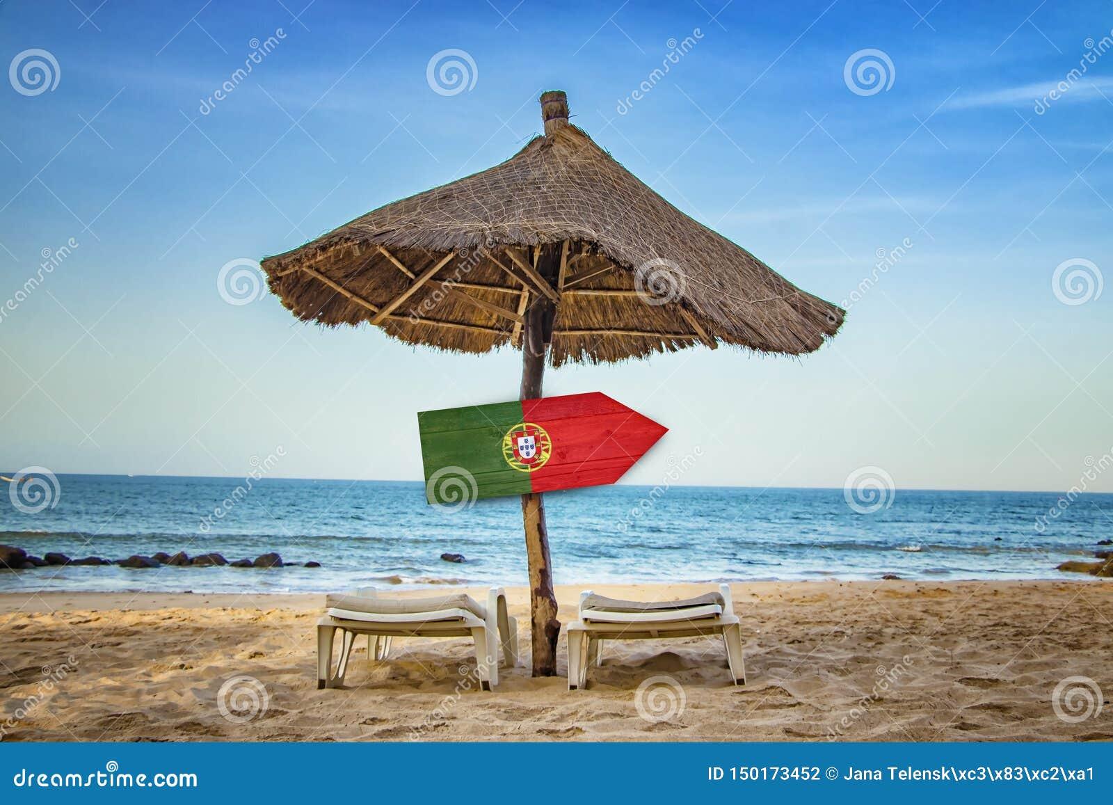 Bandeira portuguesa no sinal de madeira da seta Há dois vadios do sol e um guarda-chuva de sol na praia É um paraíso tropical com
