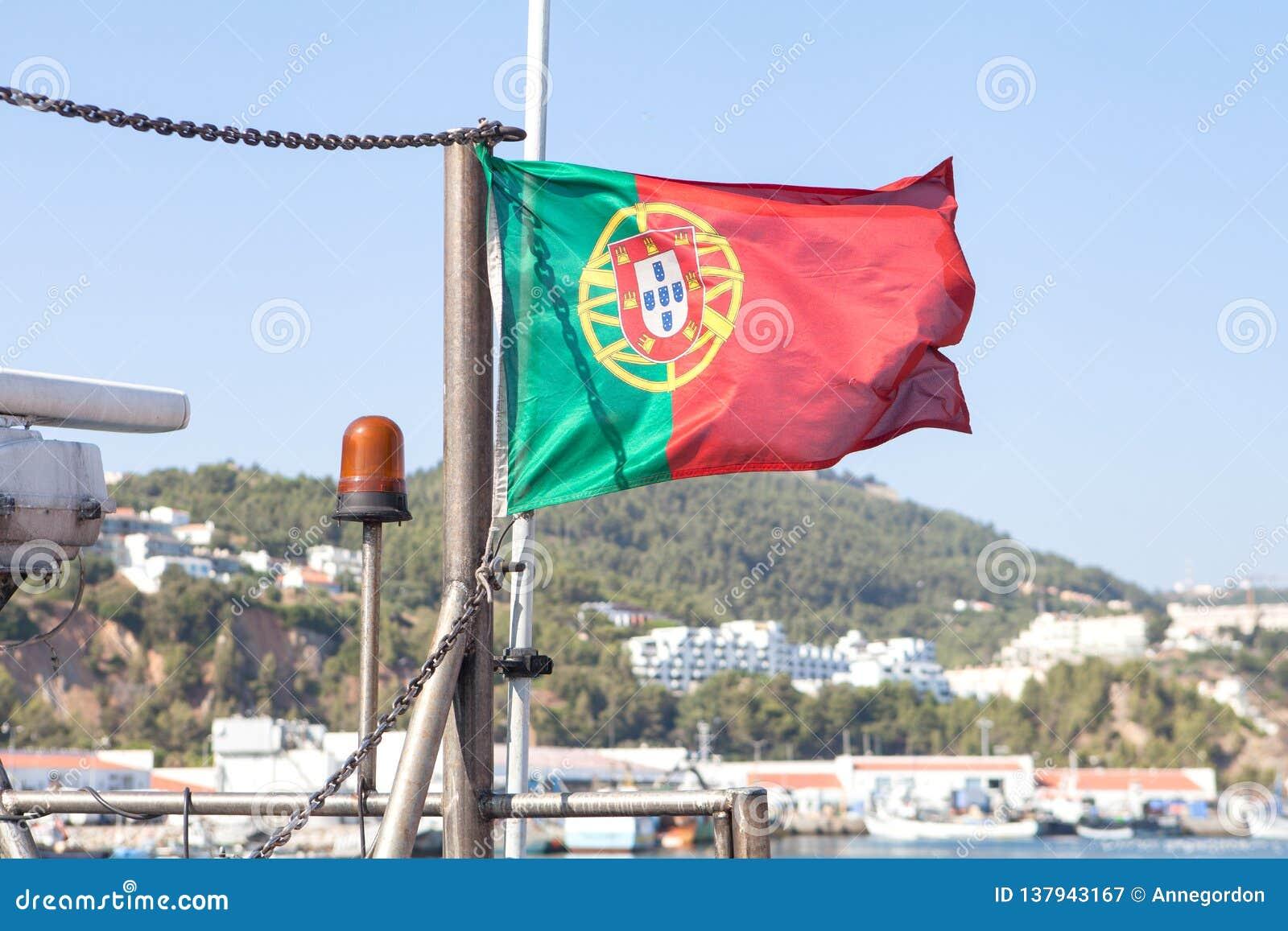 Bandeira portuguesa que acena perto do mar