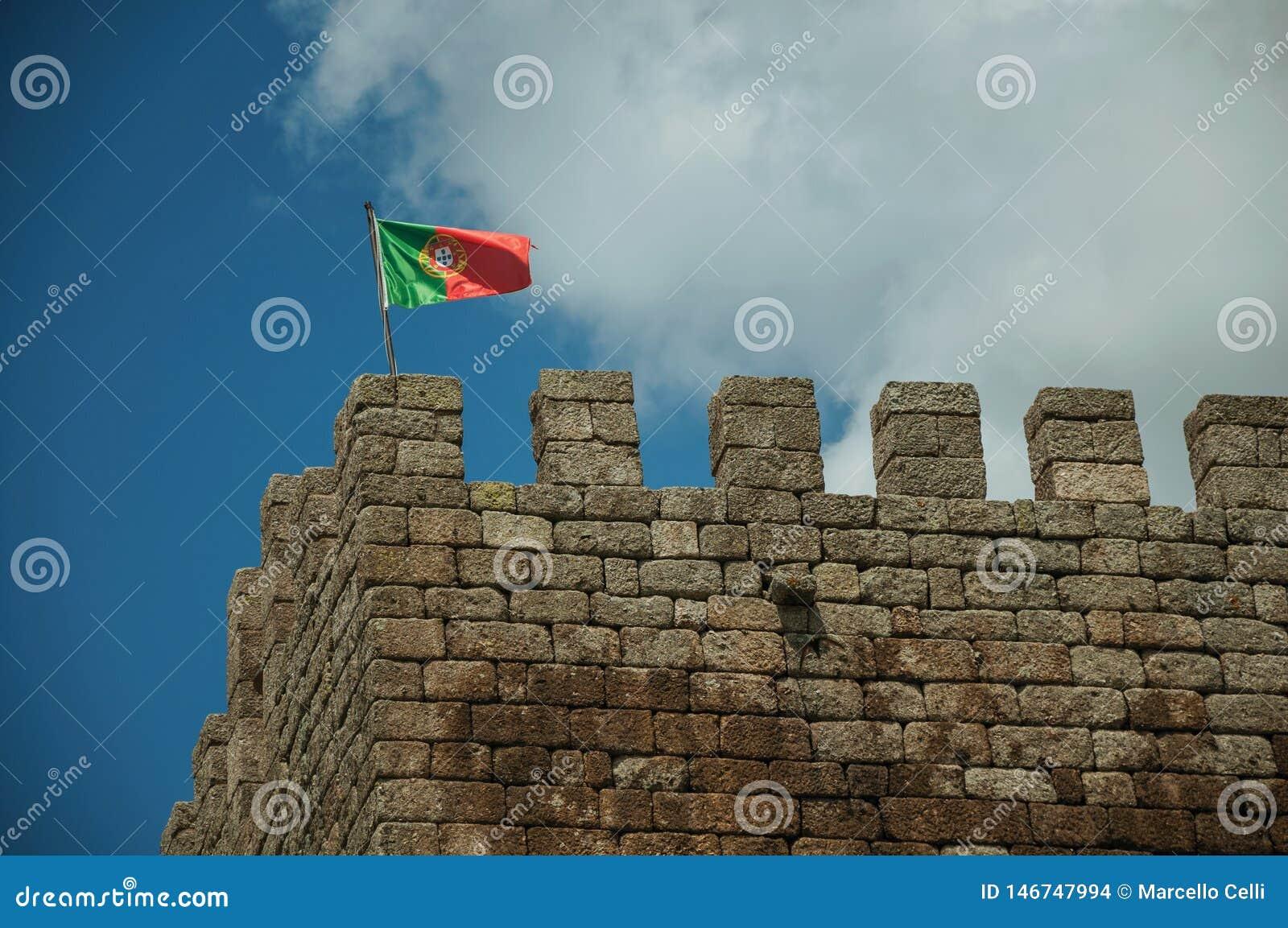 Bandeira portuguesa que vibra sobre a torre do castelo