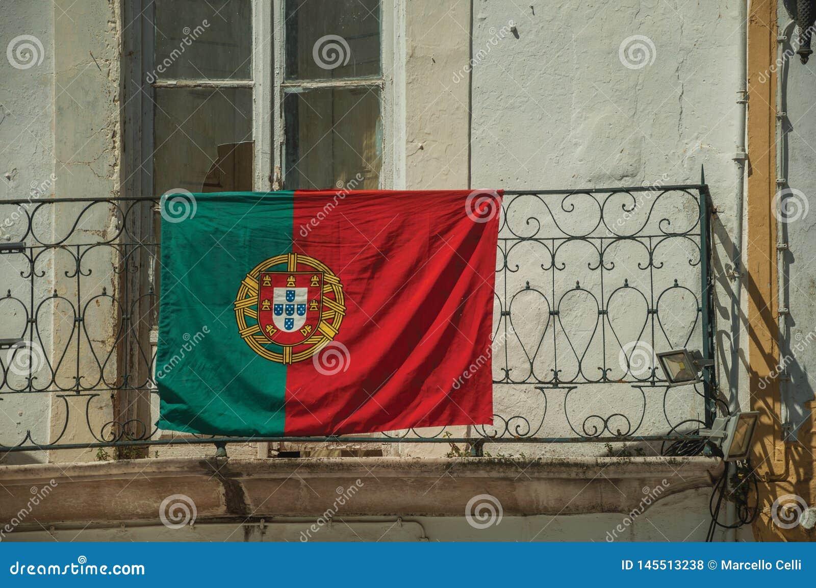 Bandeira portuguesa sobre o corrimão do ferro do balcão
