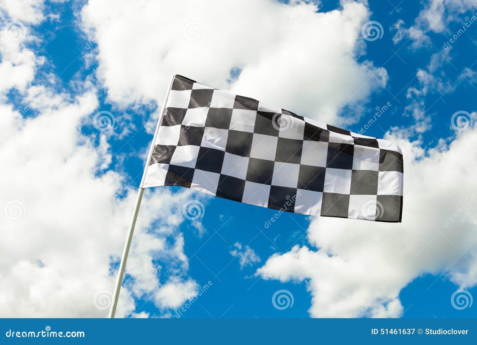 Bandeira quadriculado que acena no vento com as nuvens no fundo - dispare fora