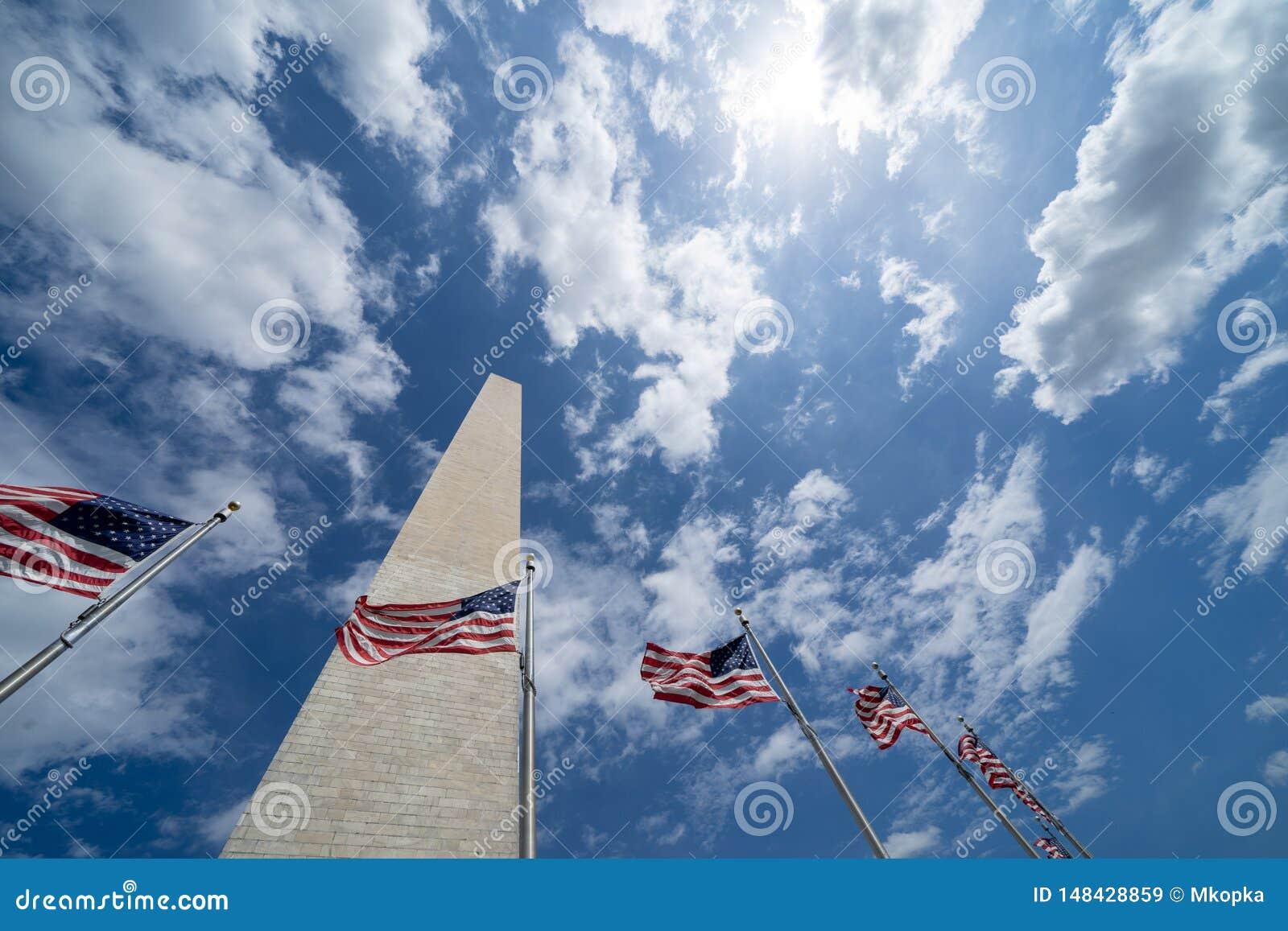 Bandeiras americanas que fundem no vento com Washington Monument ao longo do National Mall C?u em parte nebuloso