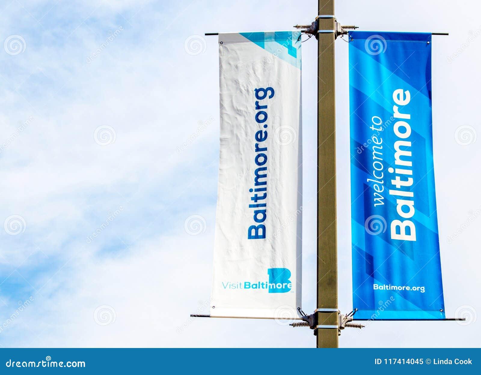 Bandeiras bem-vindas em um cargo da lâmpada no porto interno do ` s de Baltimore