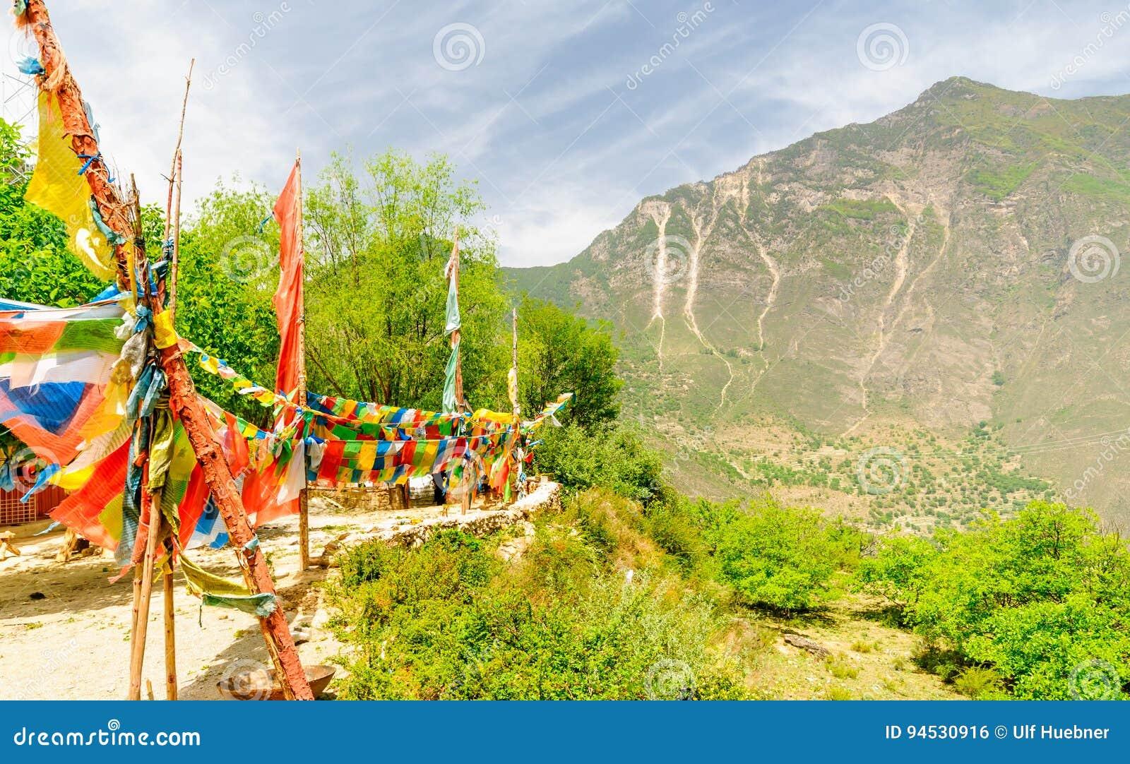 Bandeiras coloridas da oração em montanhas de Tibetand