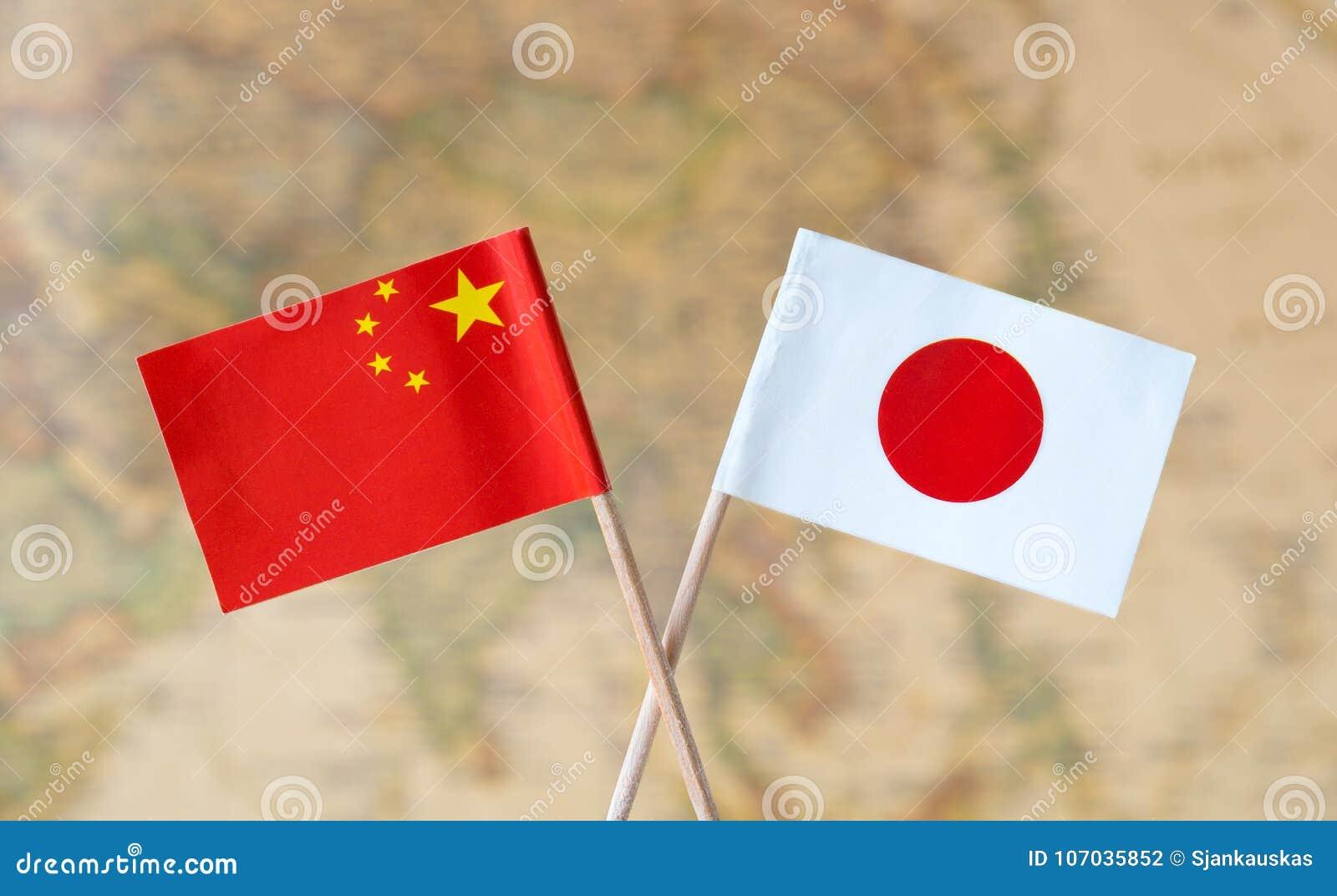 Bandeiras de China e de Japão sobre o mapa do mundo, imagem do conceito das relações políticas