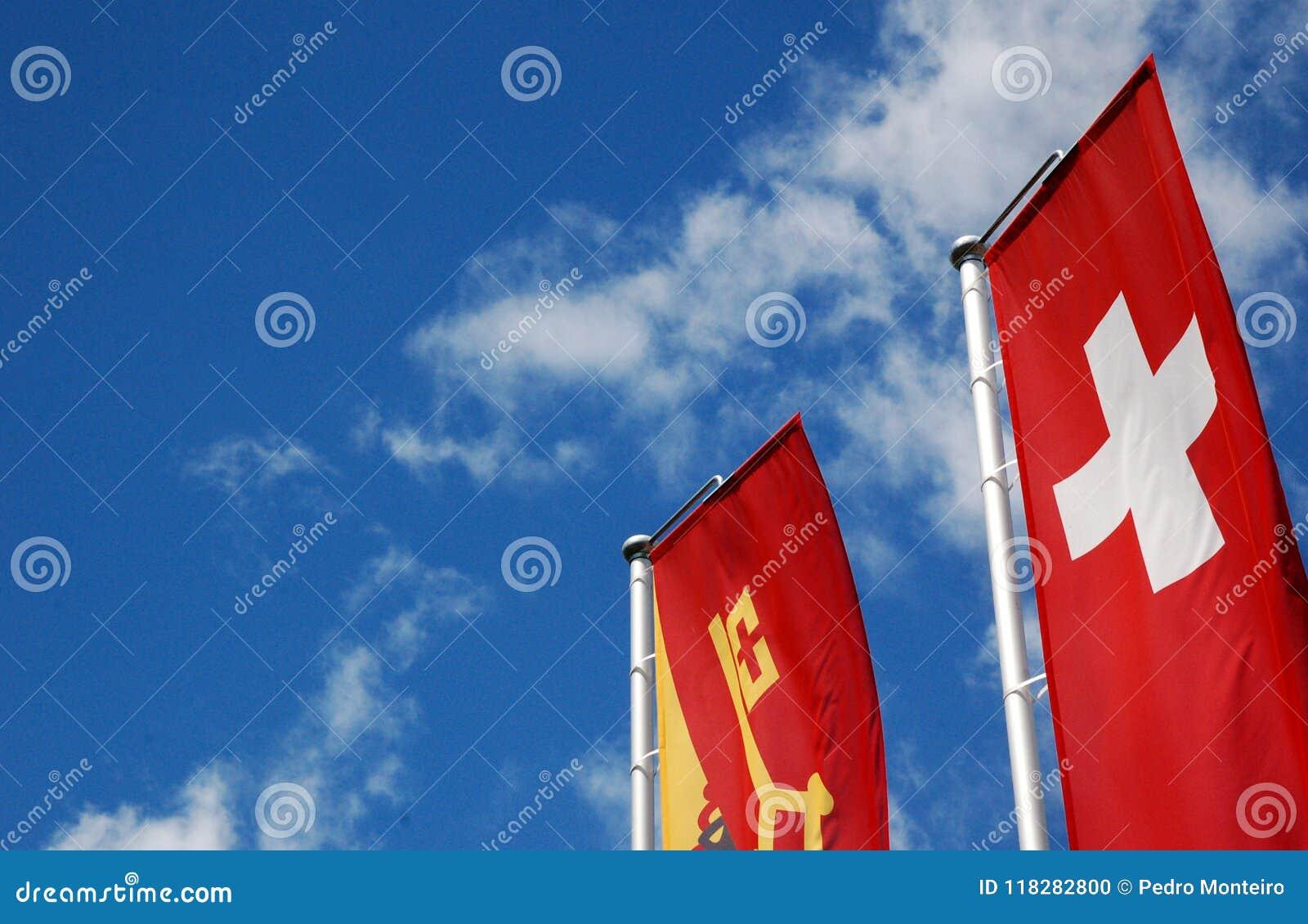 Bandeiras do cantão do suíço e da Genebra no céu ensolarado