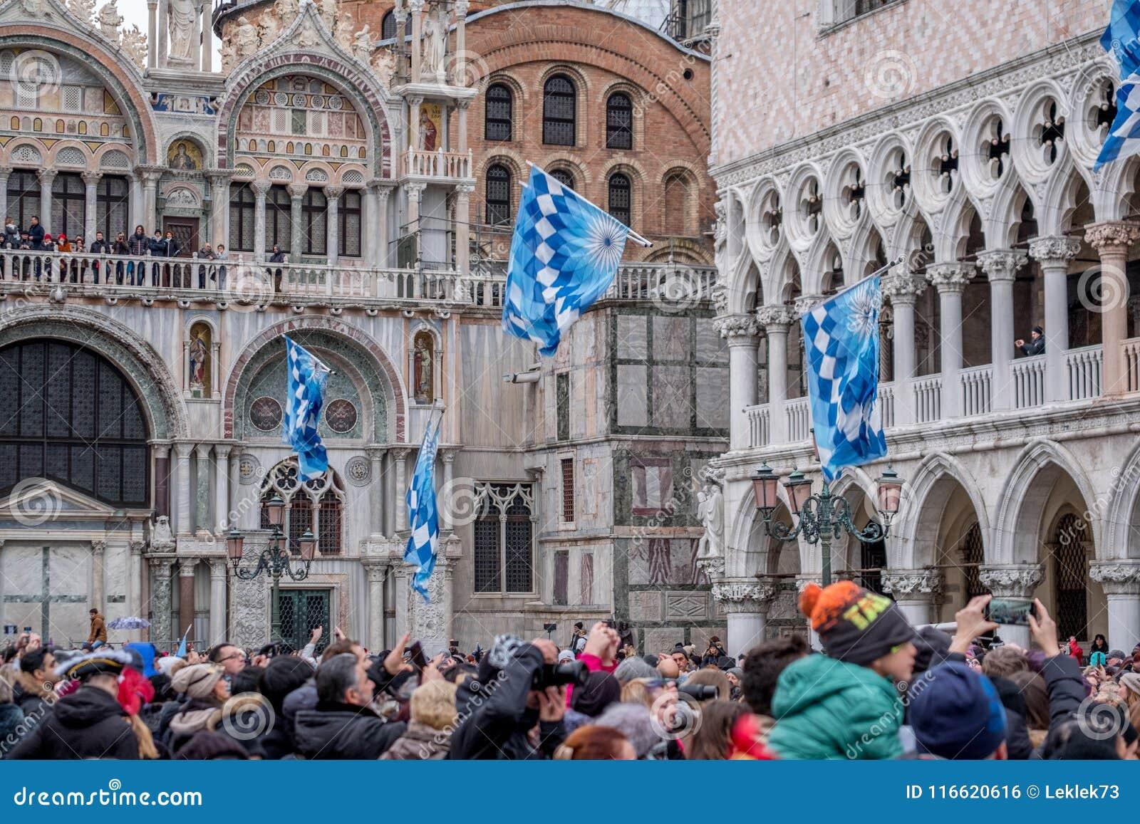 Bandeiras que estão sendo jogadas no ar no quadrado do ` s de St Mark durante a cerimônia de Maria do delle de Festa Carnaval de