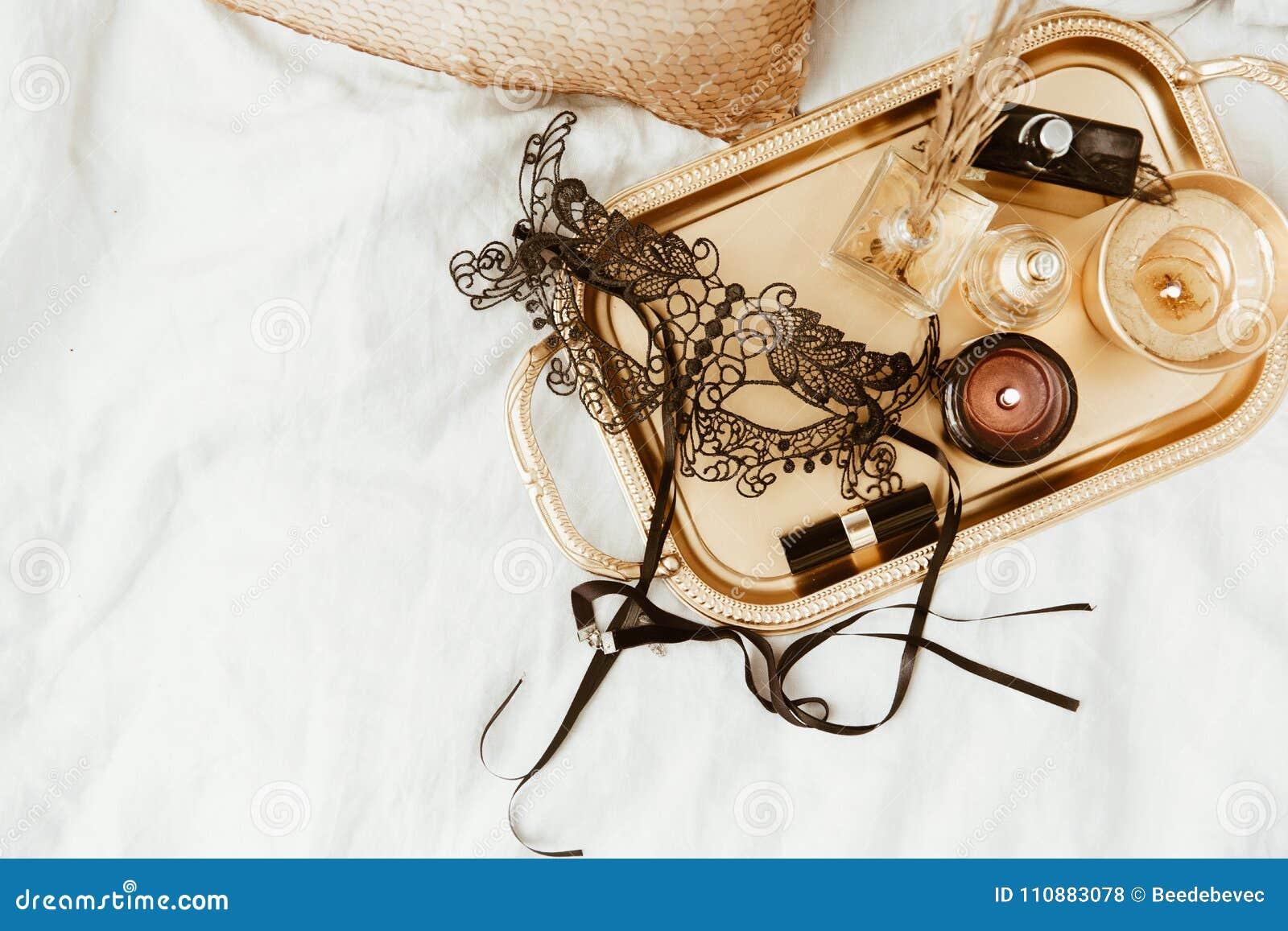 Bandeja à moda do ouro e máscara preta na cama macia fundamentos lisos da mulher da configuração por um feriado