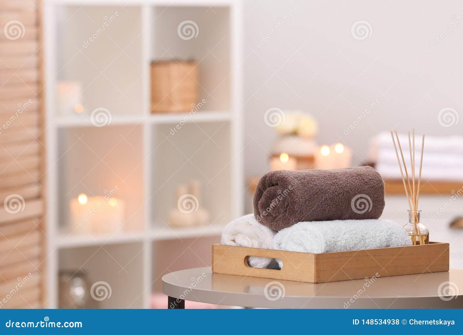Bandeja con las toallas y ambientador de aire de lámina en la tabla en salón del balneario