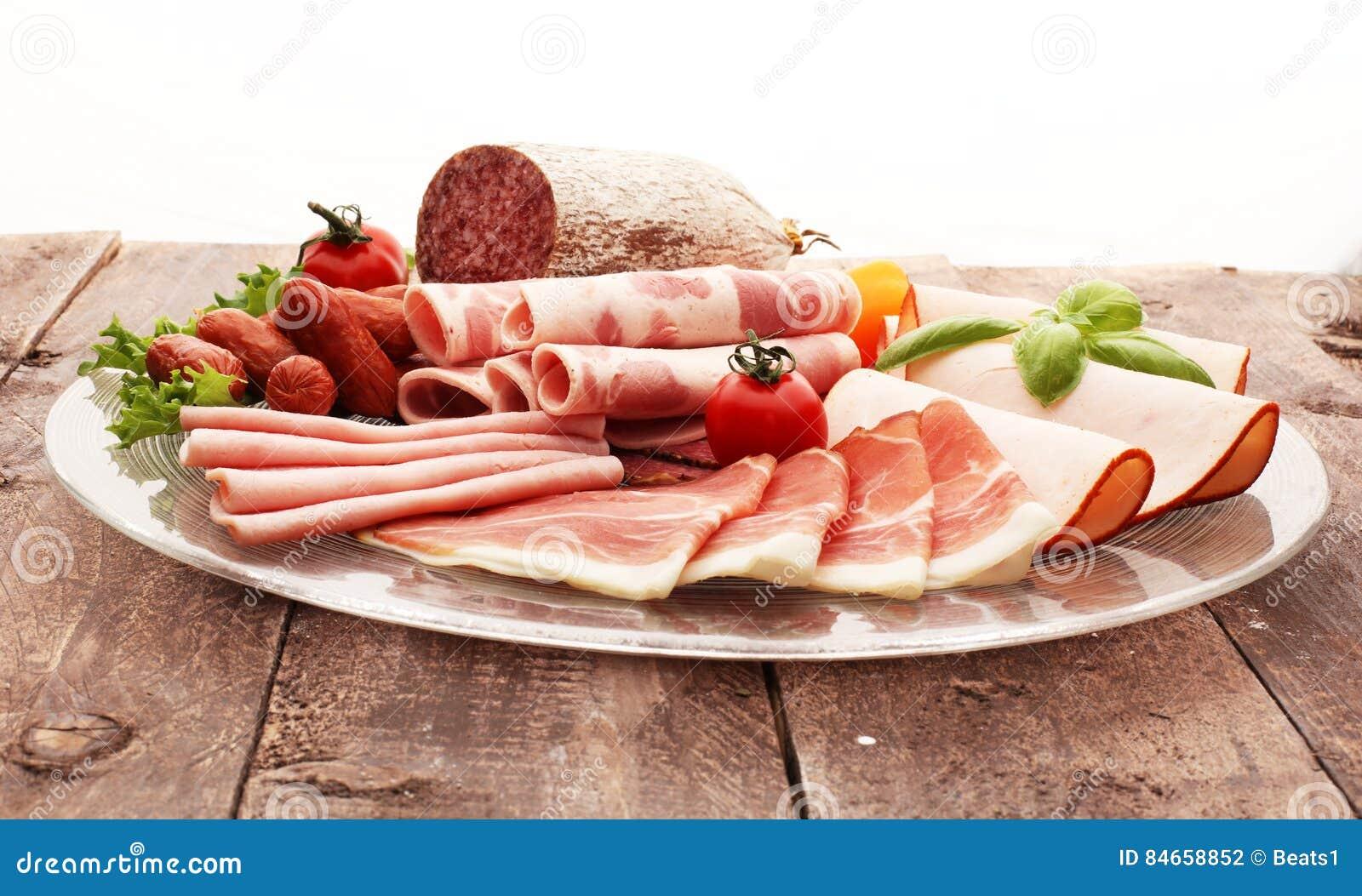 Bandeja de la comida con el salami delicioso, los pedazos de jamón cortado, la salchicha, los tomates, la ensalada y la verdura -