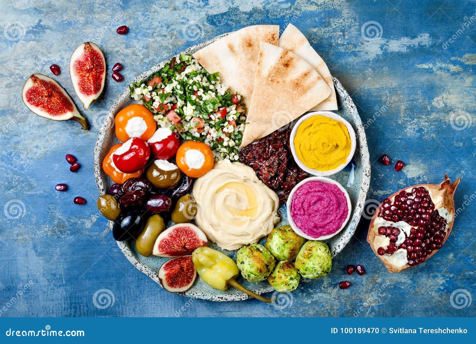 A bandeja do Oriente Médio do meze com falafel verde, pão árabe, sol secou tomates, abóbora, hummus da beterraba, azeitonas, pime