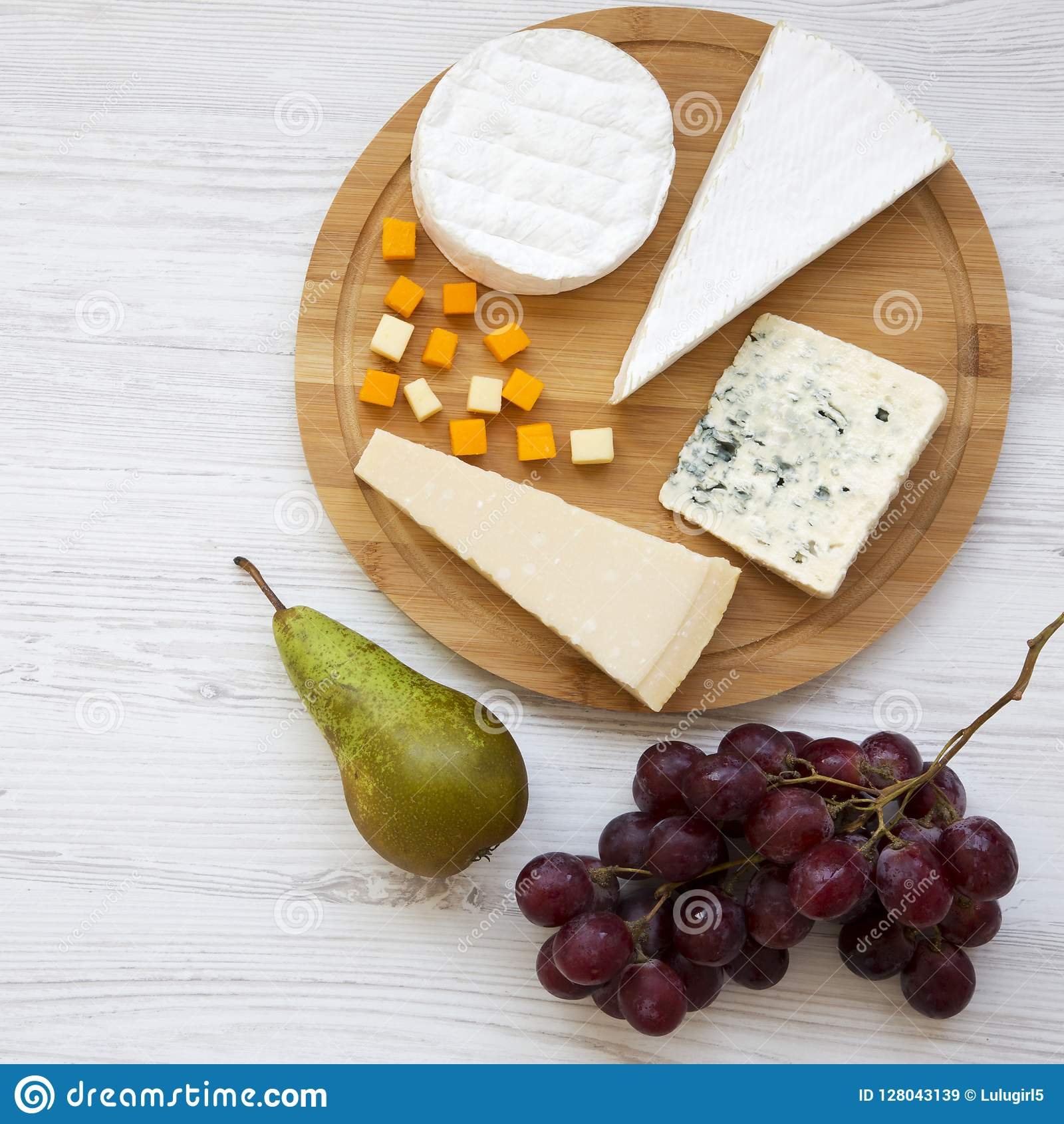 Bandeja do queijo com frutos em um fundo de madeira branco Alimento para o vinho, vista superior Configuração lisa, de cima de Cl