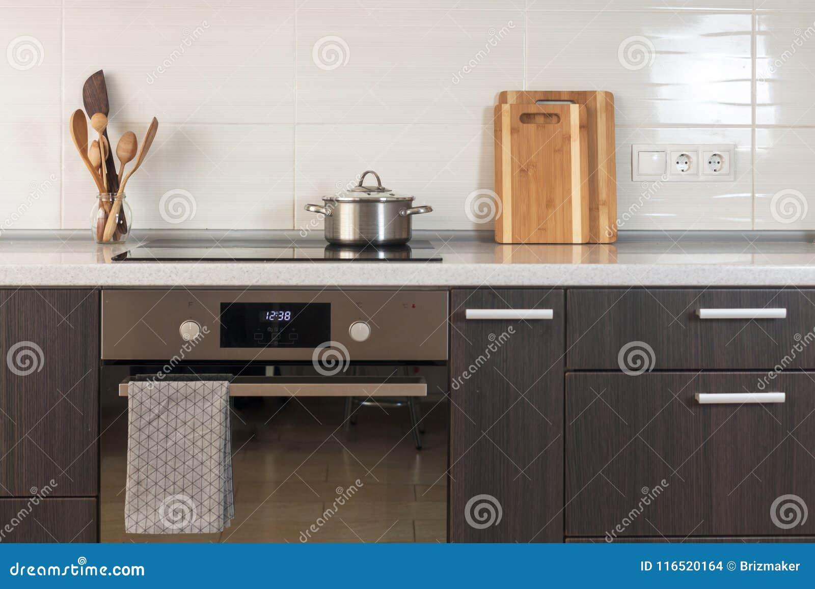 A bandeja está em um fogão cerâmico Cozinha clara com forno, placa de corte e outros elementos de utensílios da cozinha