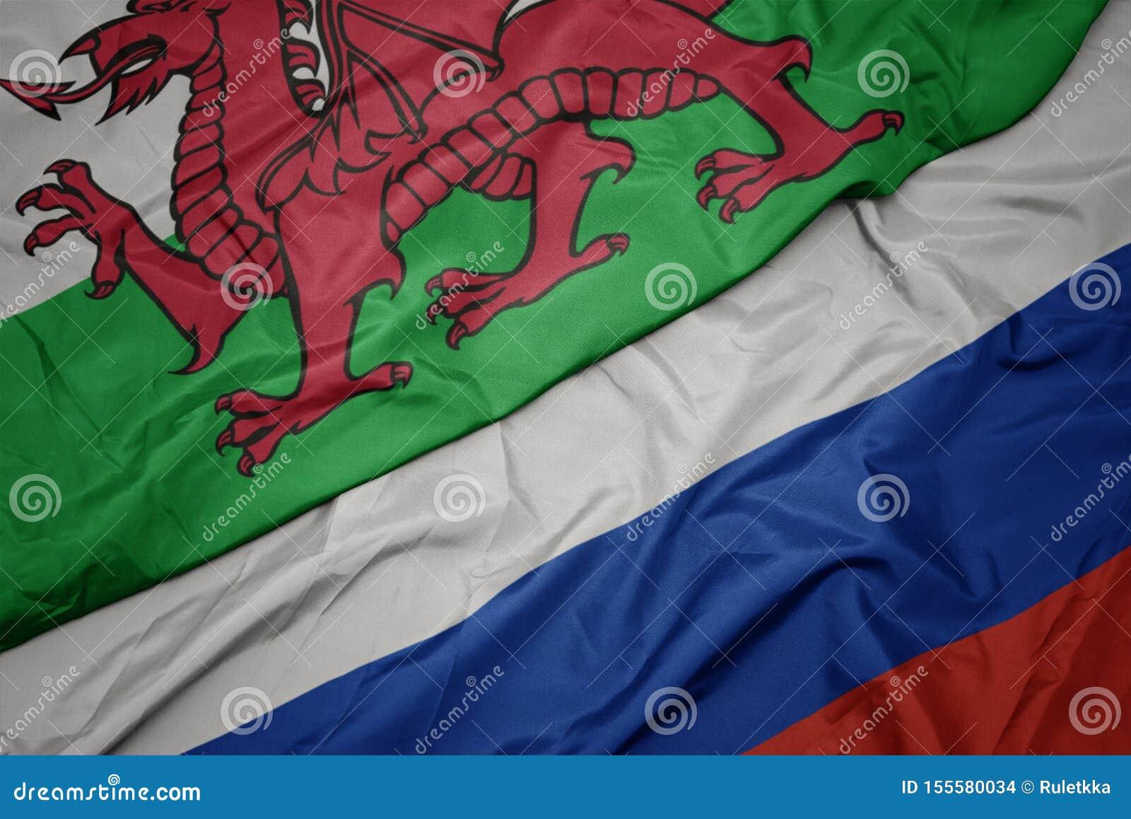 Bandera colorida que agita de Rusia y bandera nacional de País de Gales