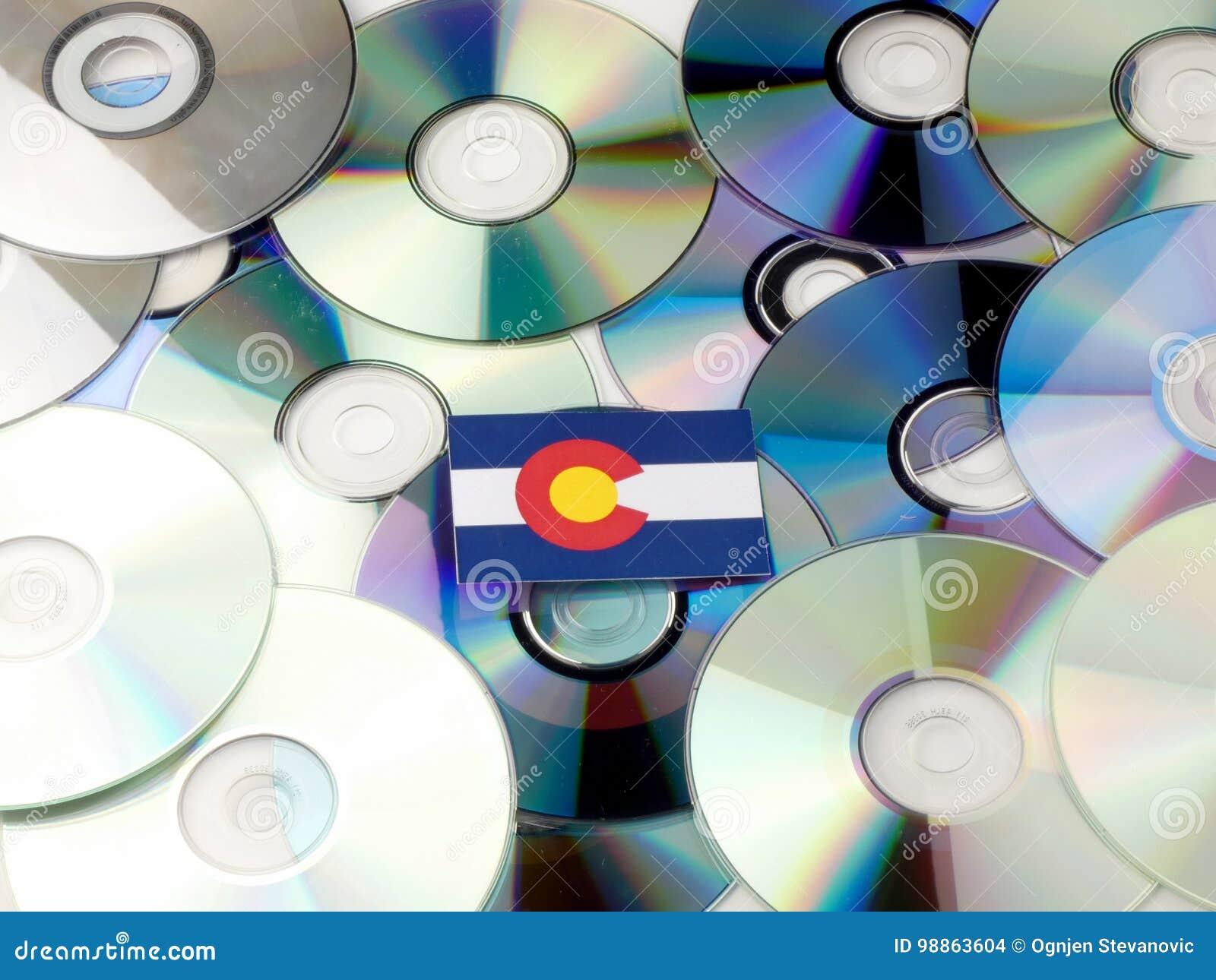 Bandera de Colorado encima de la pila del CD y del DVD aislada en blanco
