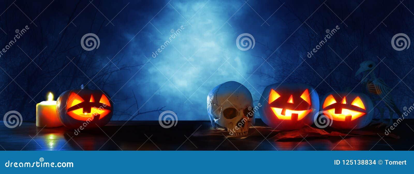 Bandera del concepto del día de fiesta de Halloween Calabazas sobre la tabla de madera en el bosque asustadizo, frecuentado y bru