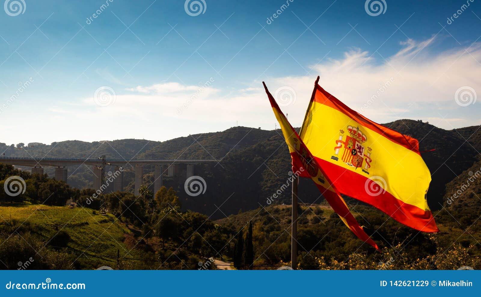 Bandera española con el cielo azul y el puente