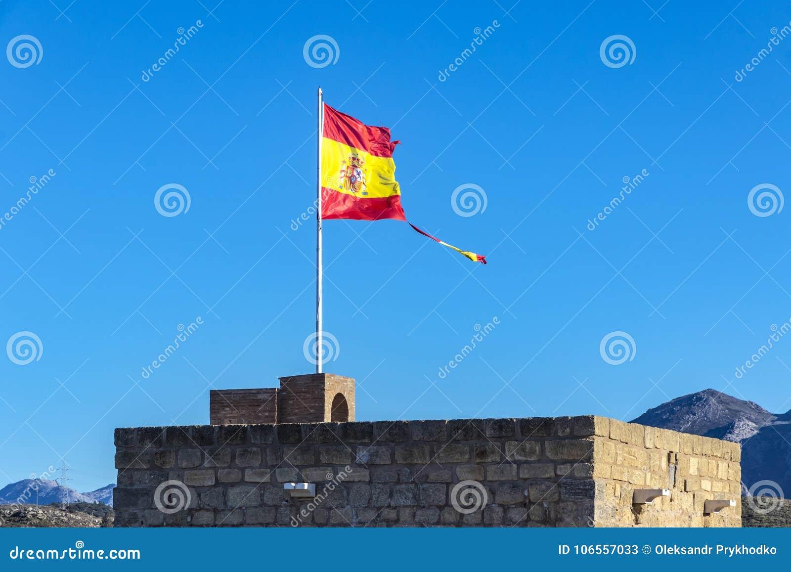 Bandera española rasgada que agita en el viento