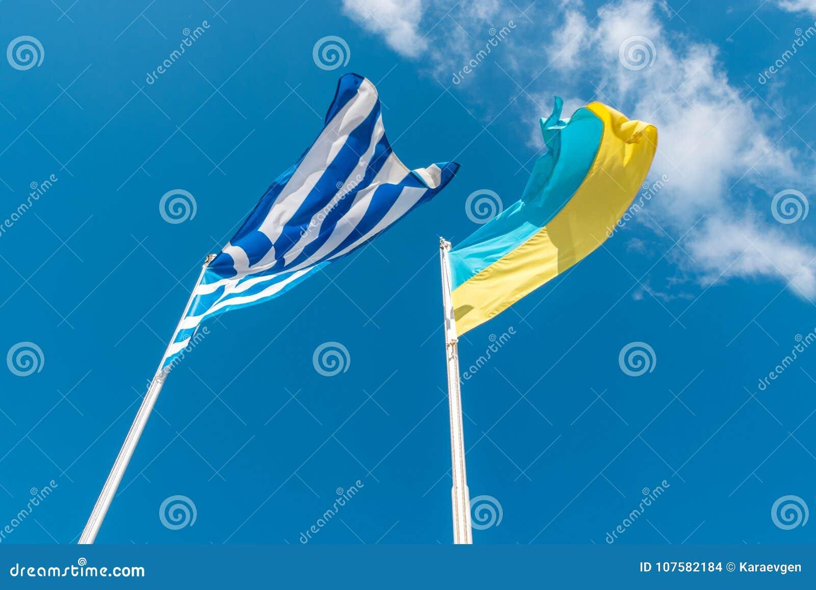 Bandera ucraniana con la bandera griega en el fondo del cielo
