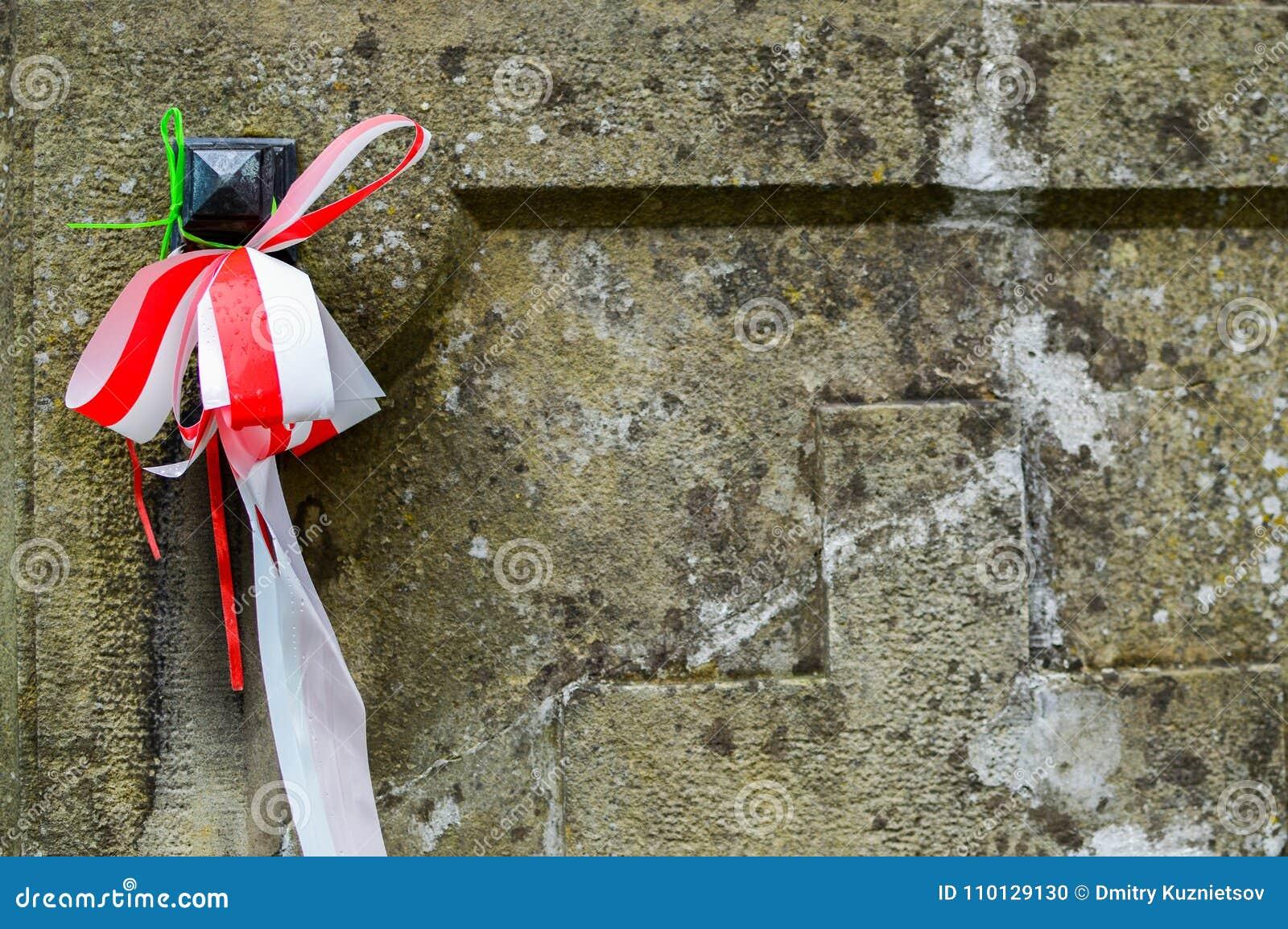 Bandet med nationella färger av Polen band upp till den gamla gravstenen på olskyrkogården Allt helgondagbegrepp
