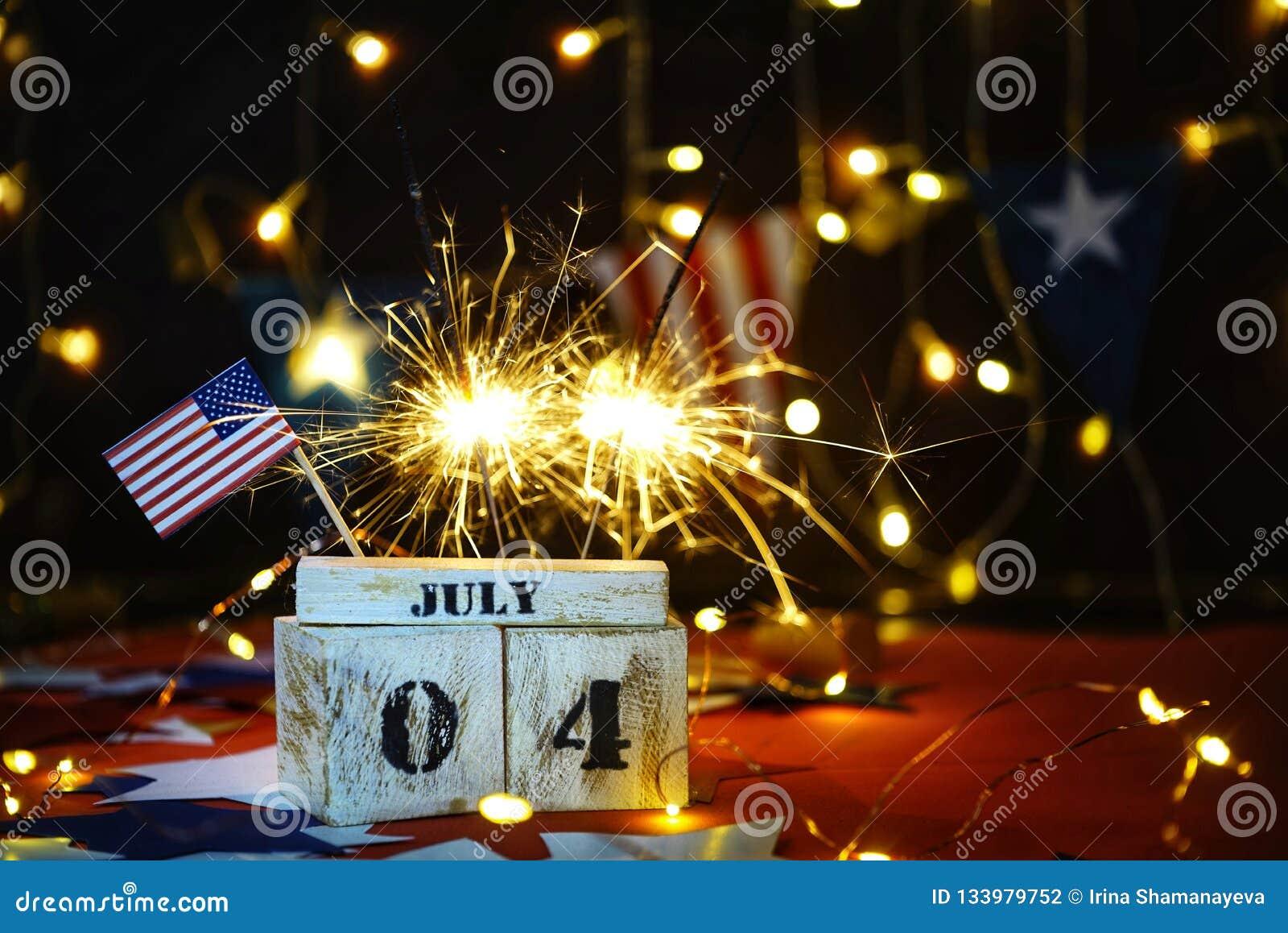 Bandiera americana increspata e calendario di legno del cubo con il quarto luglio, data di festa dell indipendenza di U.S.A., fon