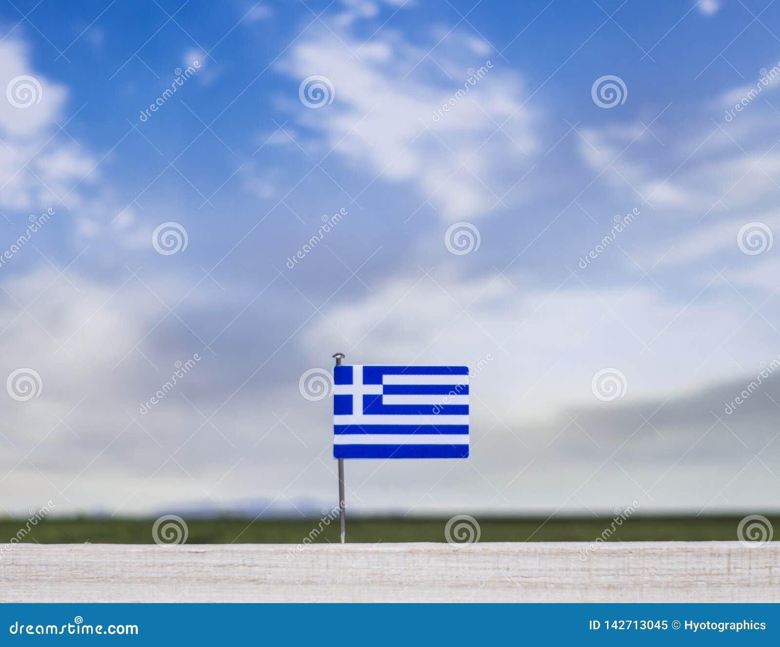 Bandiera della Grecia con il vasti prato e cielo blu dietro