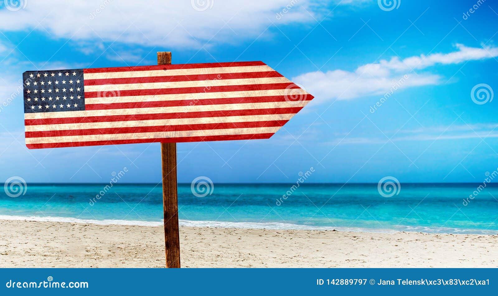 Bandiera di U.S.A. sul segno di legno della tavola sul fondo della spiaggia È segno dell estate di U.S.A.