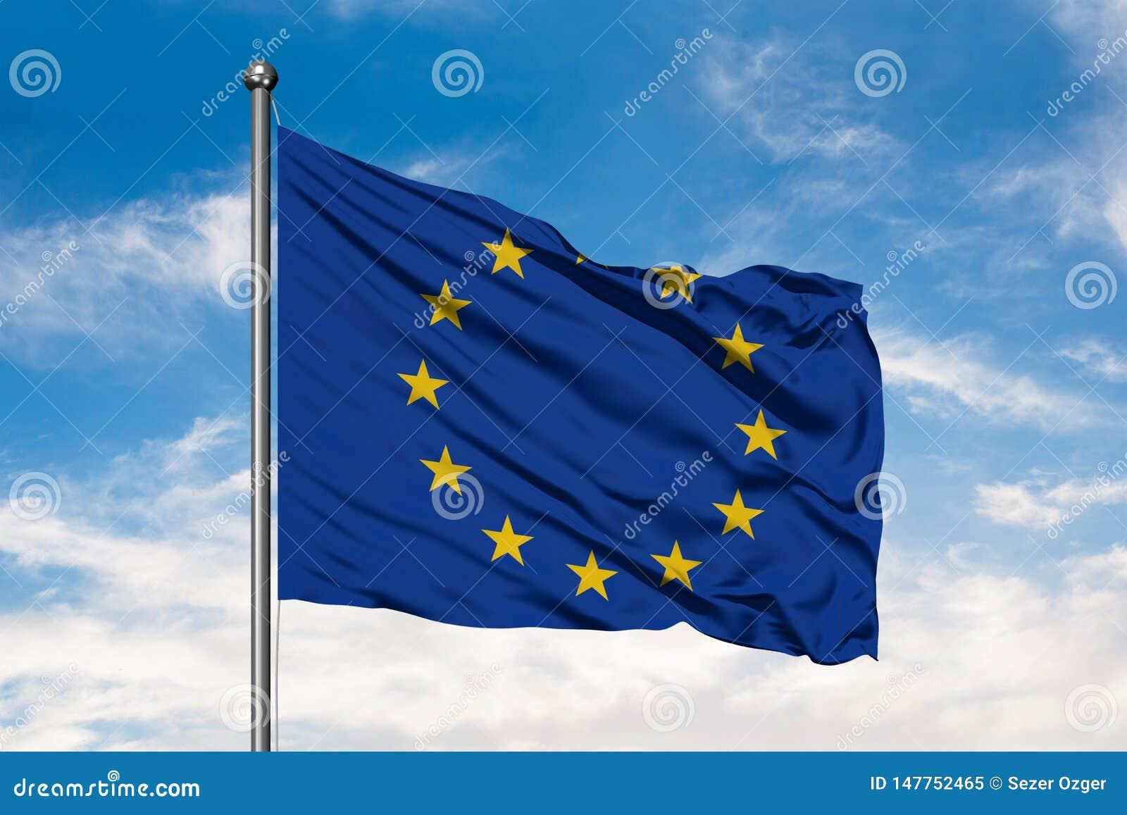 Bandiera di Unione Europea che ondeggia nel vento contro il cielo blu nuvoloso bianco