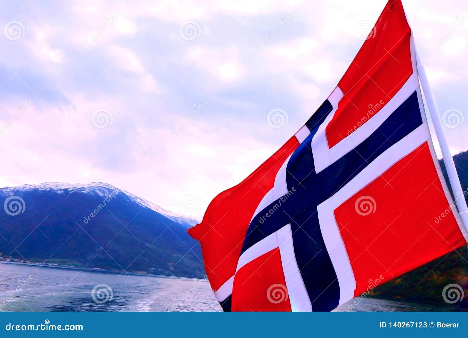 Bandiera norvegese d ondeggiamento sul fiordo circondato dal fondo delle montagne