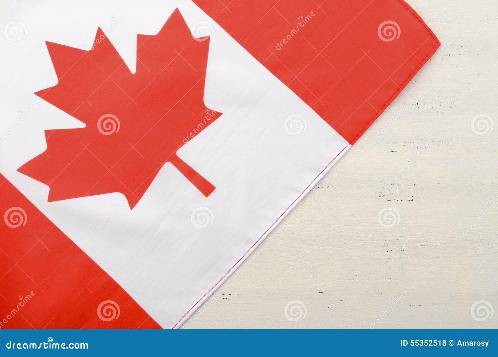 Bandiera rossa canadese della foglia di acero su fondo di legno bianco