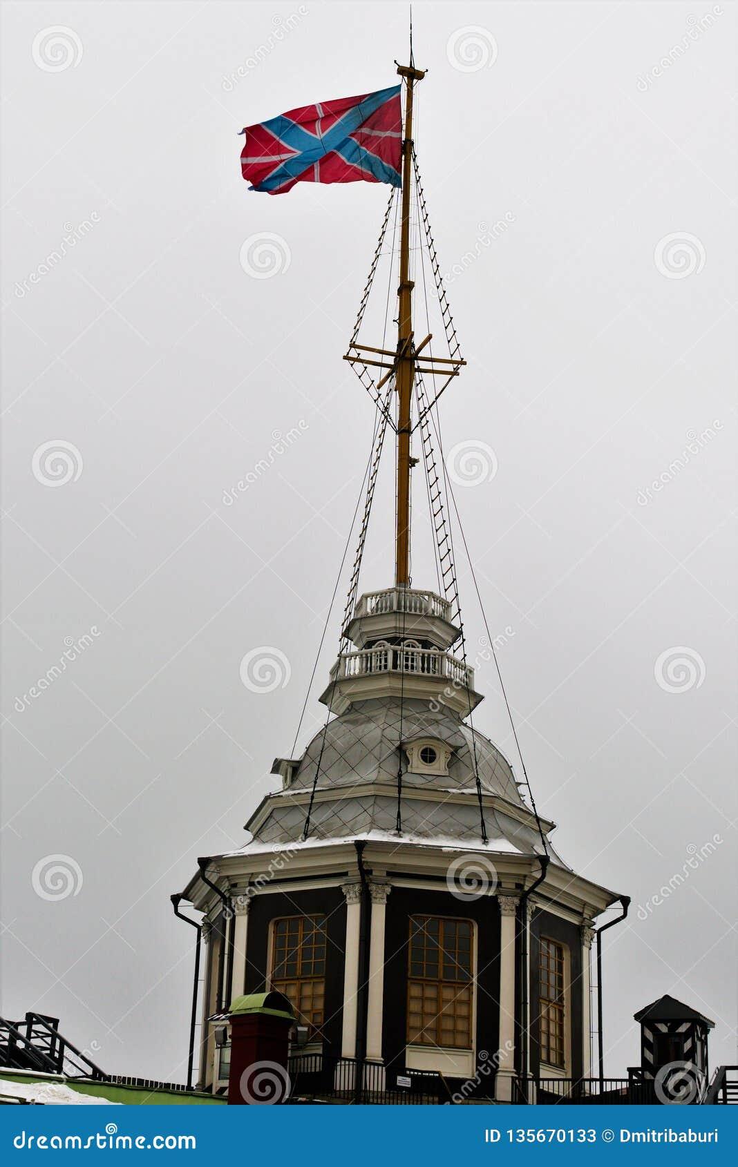 Bandiera russa di St Andrew sopra la torre nel Peter ed in Paul Fortress a St Petersburg, Russia