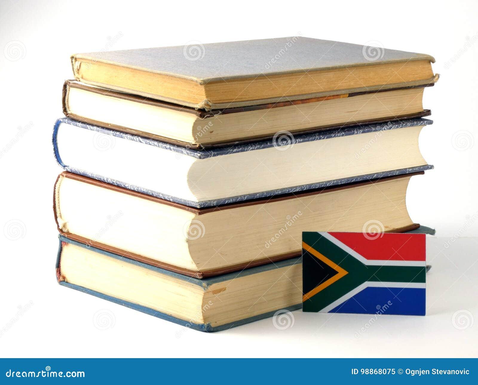 Bandiera sudafricana con il mucchio dei libri isolati sul backgrou bianco