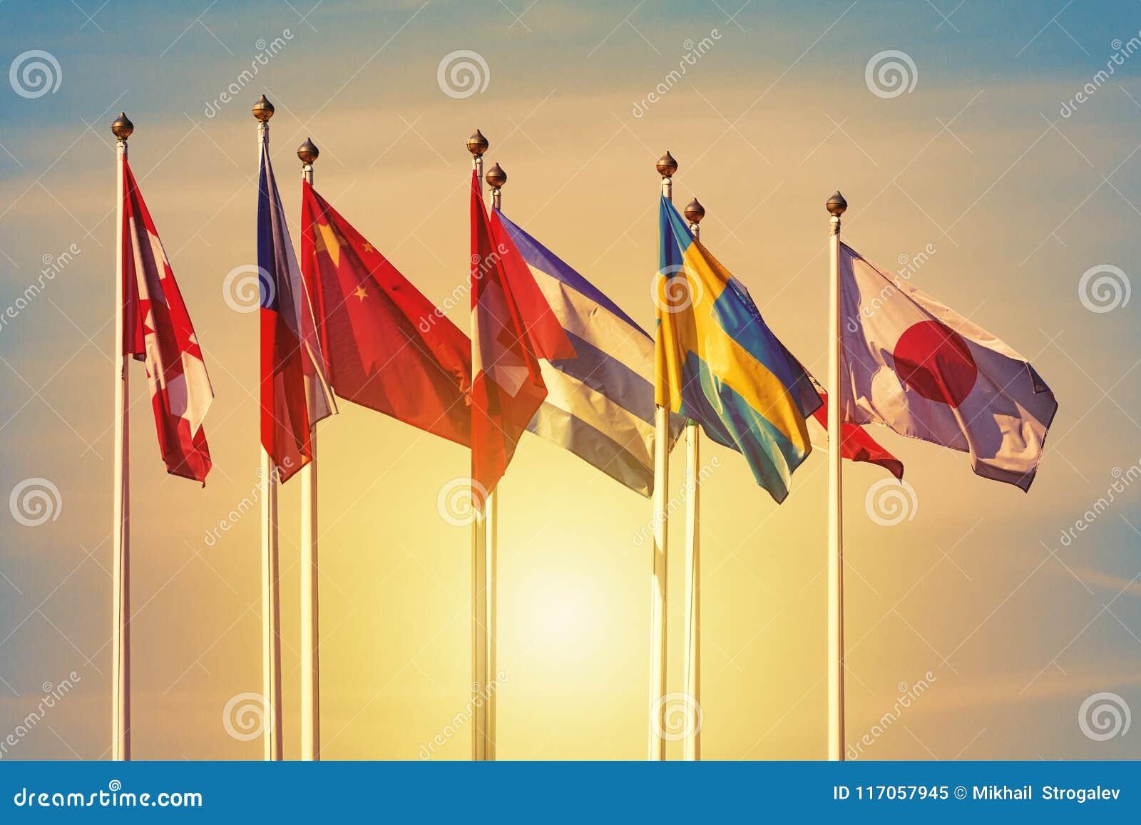 Bandiere dei paesi differenti contro un tramonto