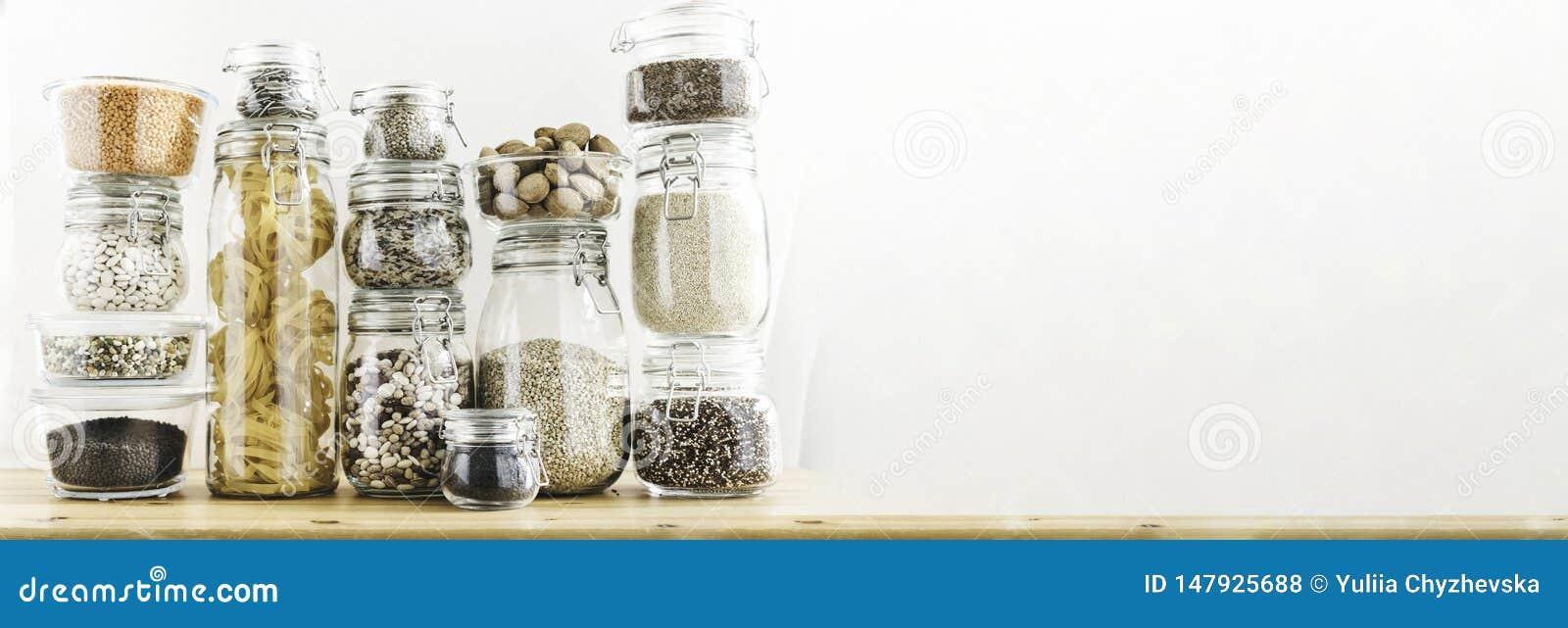 Baner med sortimentet av kornprodukter och pasta i exponeringsglaslagringsbehållare på trätabellen Sunt laga mat som är rent