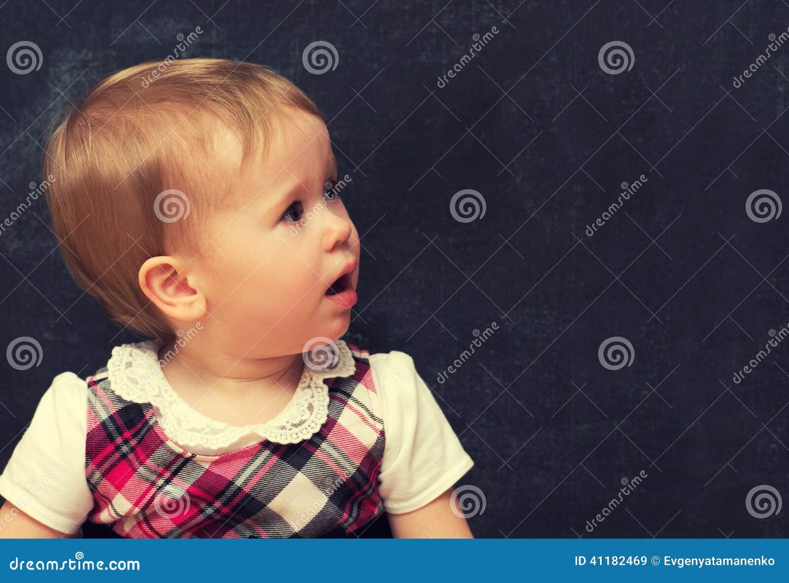 Bang gemaakt babymeisje met krijt bij een schoolraad