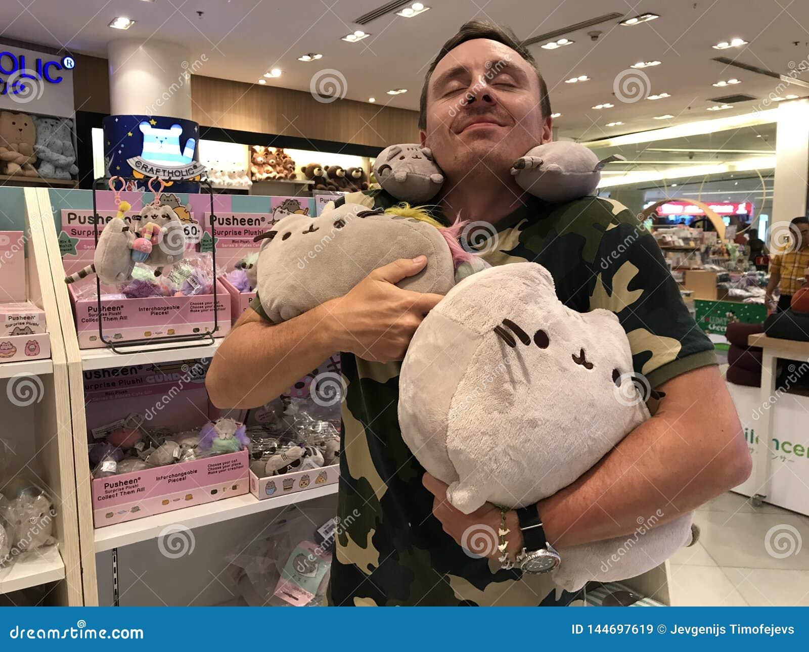 BANGKOK, TAILANDIA - 16 DE ABRIL DE 2018: El hombre goza de los juguetes del gato de la felpa de Pusheen en Asia