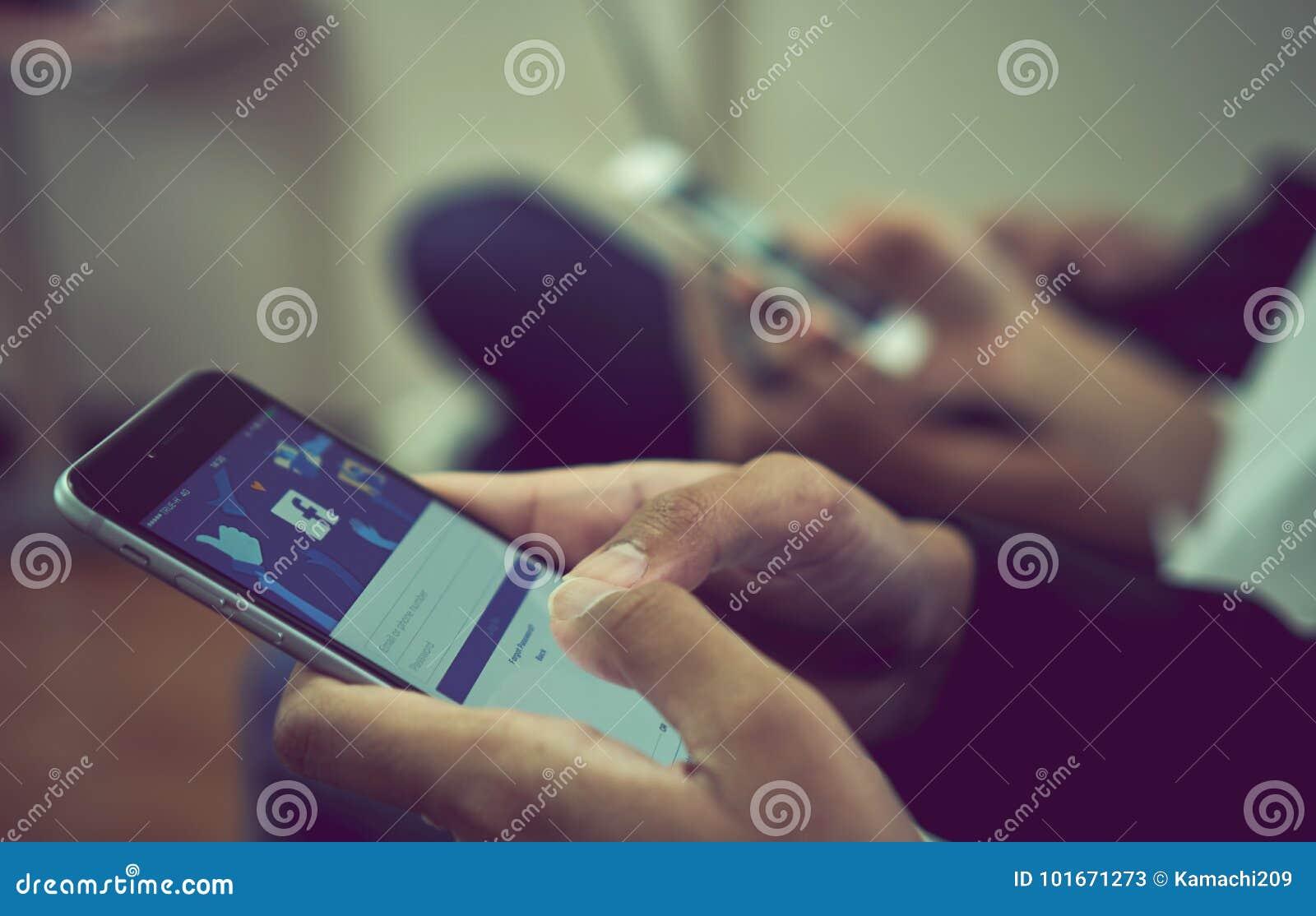 Bangkok, Tailandia - 11 de octubre de 2017: la mano está presionando la pantalla de Facebook en la manzana iphone6