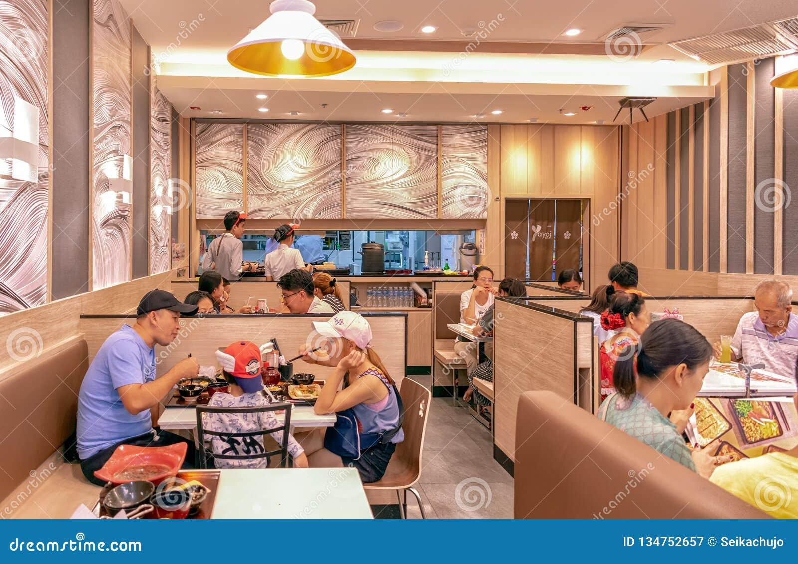 BANGKOK TAJLANDIA, GRUDZIEŃ, - 16: Niezidentyfikowana Azjatycka rodzina cieszy się jedzenie w Yayoi Japońskiej restauracji w BicC