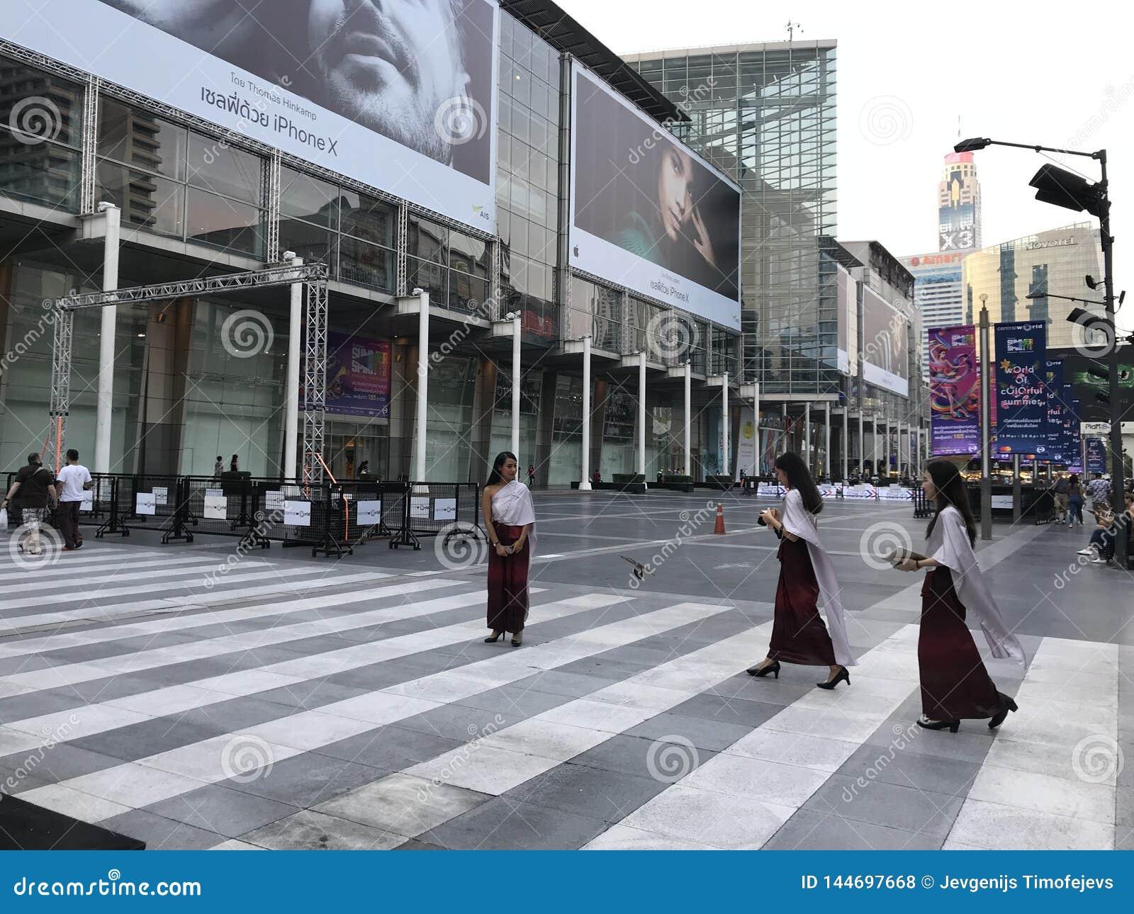 BANGKOK TAJLANDIA, KWIECIEŃ, - 16, 2018: Kobiety w religijnych strojach z iPhone X reklamą w tle